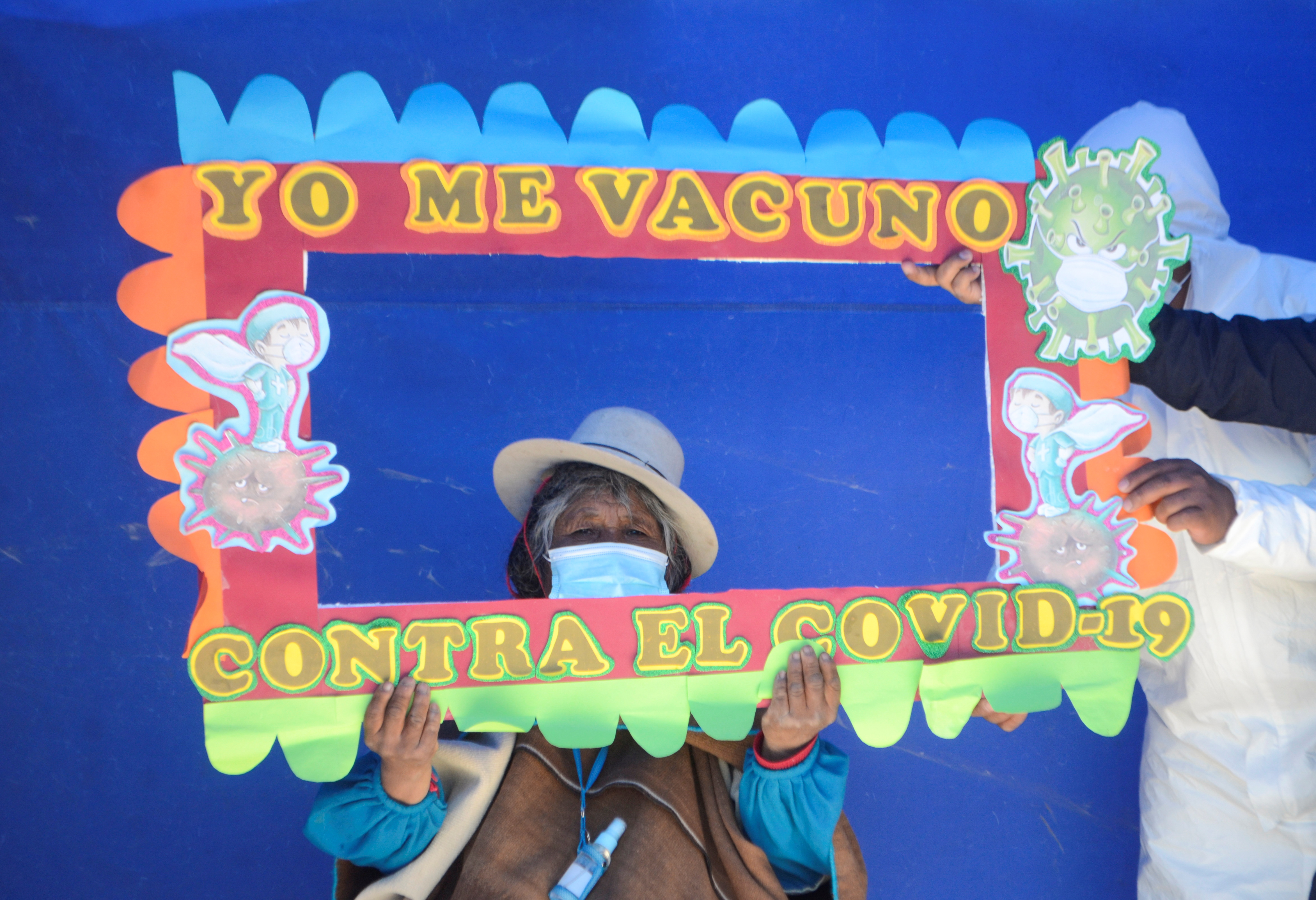 A woman who had previously received a vaccine against the coronavirus disease (COVID-19) is asked to hold a frame reading