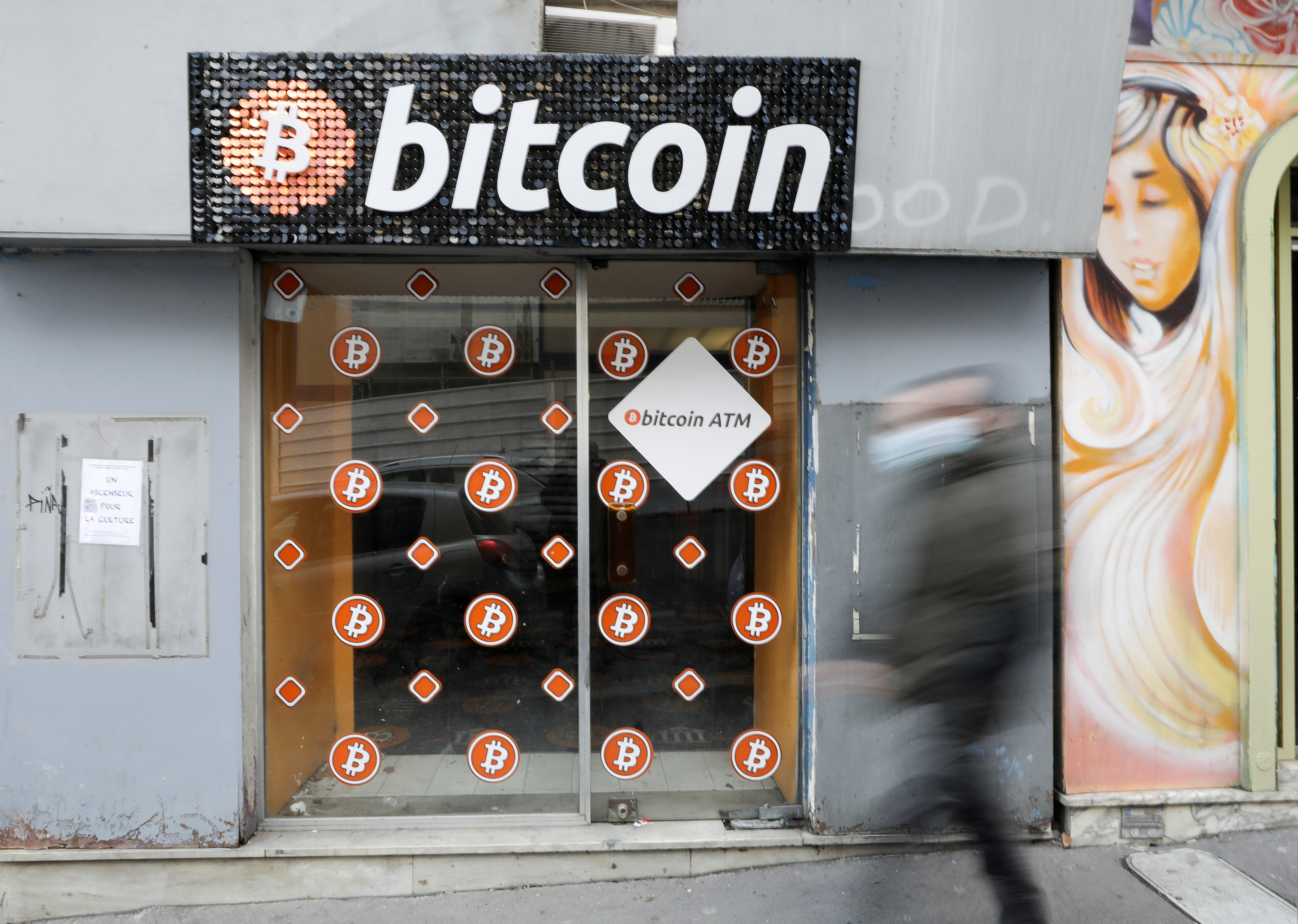 A man wearing a face mask walks past a Bitcoin digital currency ATM shop in Marseille, France, February 7, 2021. REUTERS/Eric Gaillard