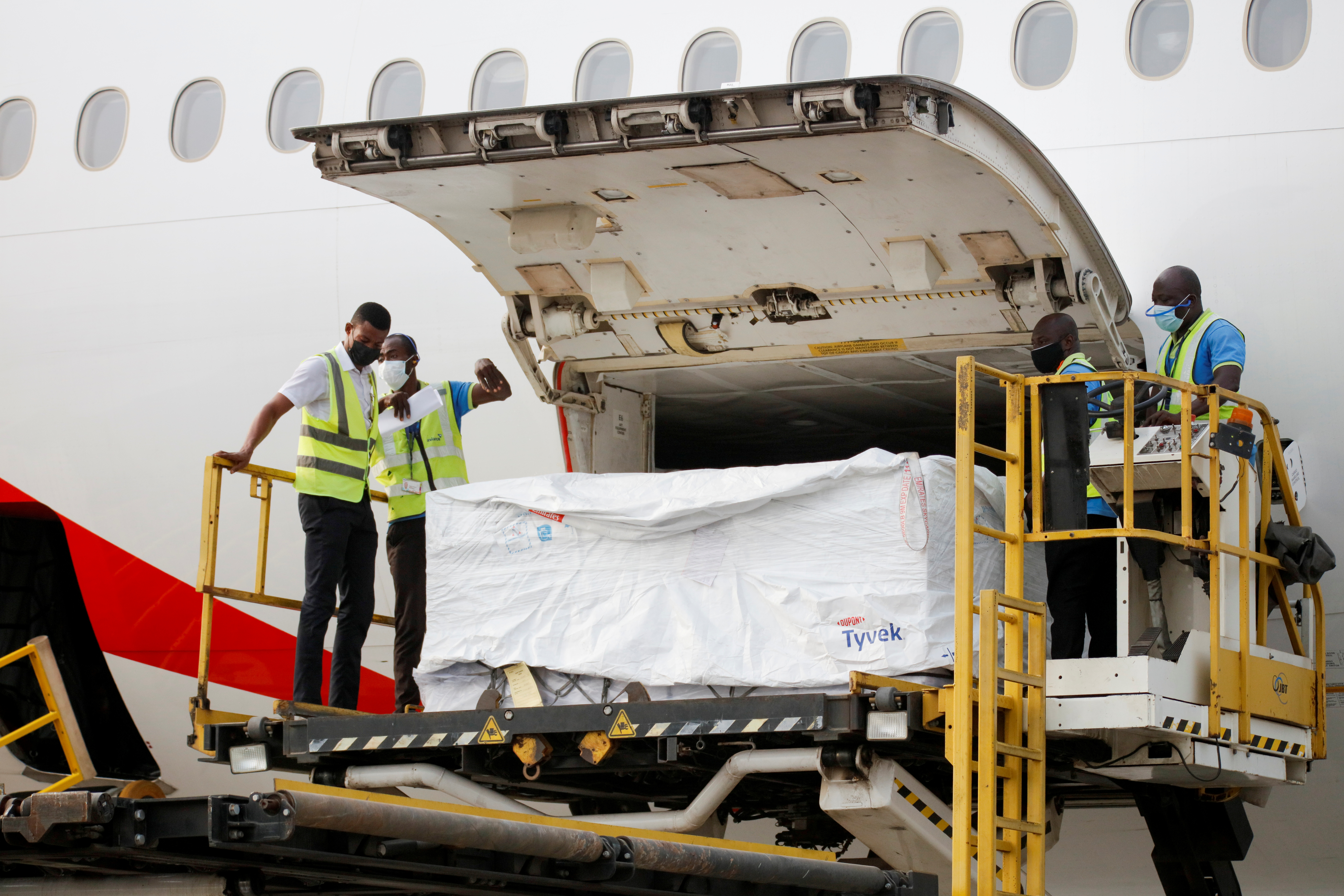 Workers offload boxes of AstraZeneca/Oxford vaccines as the country receives its first batch of coronavirus disease (COVID-19) vaccines under COVAX scheme, at the international airtport of Accra, Ghana February 24, 2021. REUTERS/Francis Kokoroko