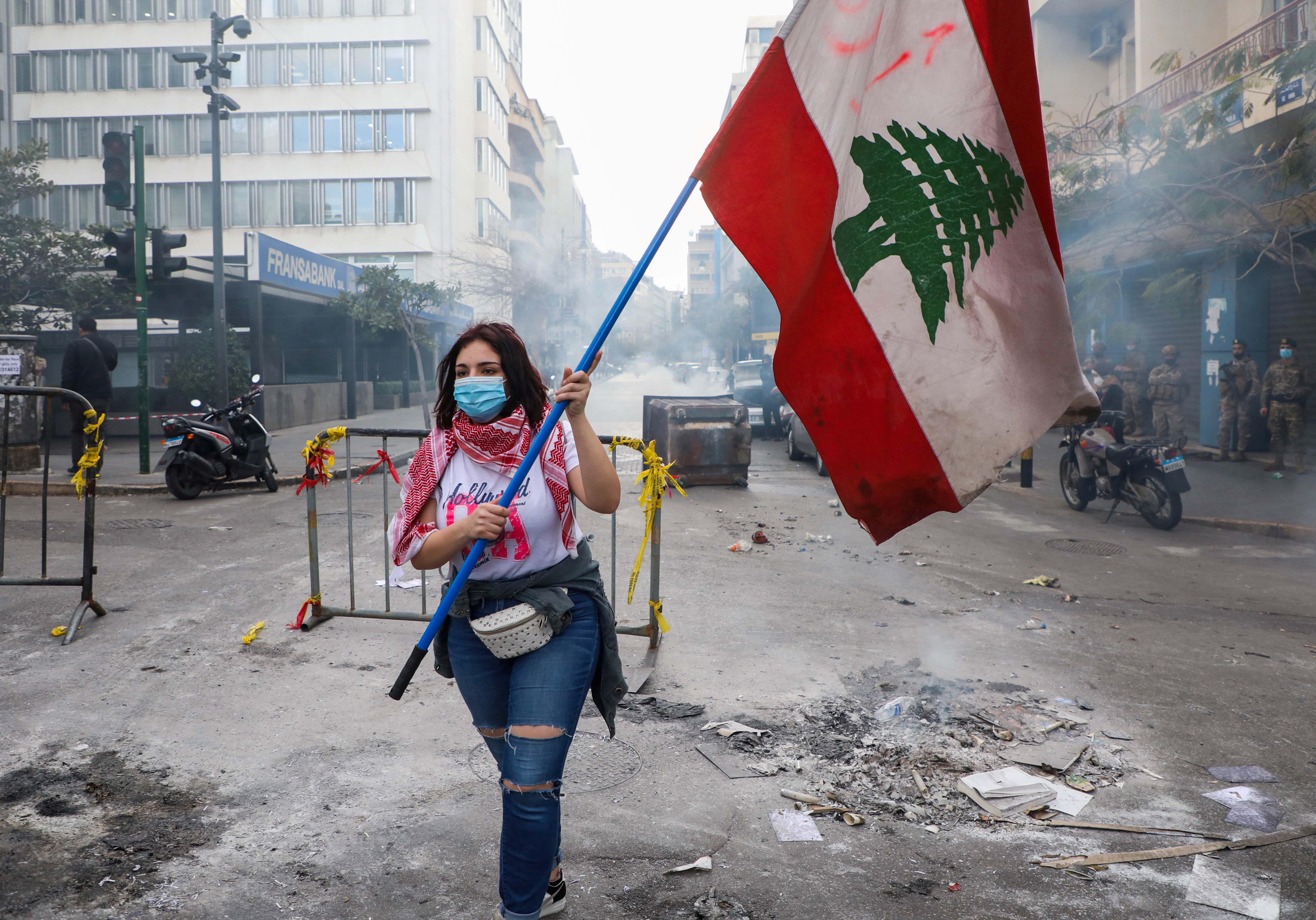 A demonstrator carries a national flag along a blocked road, during a protest against the fall in Lebanese pound currency and mounting economic hardships, near the Central Bank building, in Beirut, Lebanon March 16, 2021. REUTERS/Mohamed Azakir