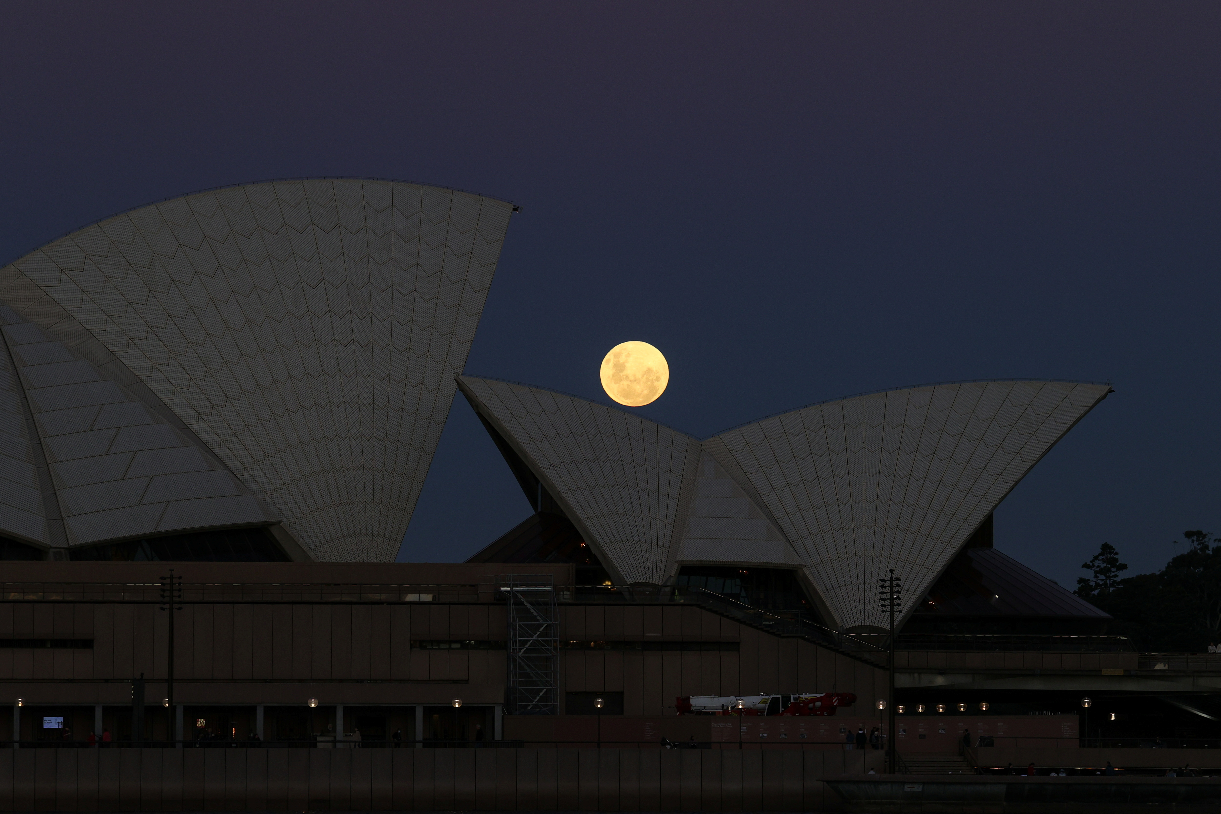 A Super Flower Moon rises behind the Sydney Opera House on the night of a lunar eclipse, in Sydney, Australia, May 26, 2021.  REUTERS/Loren Elliott