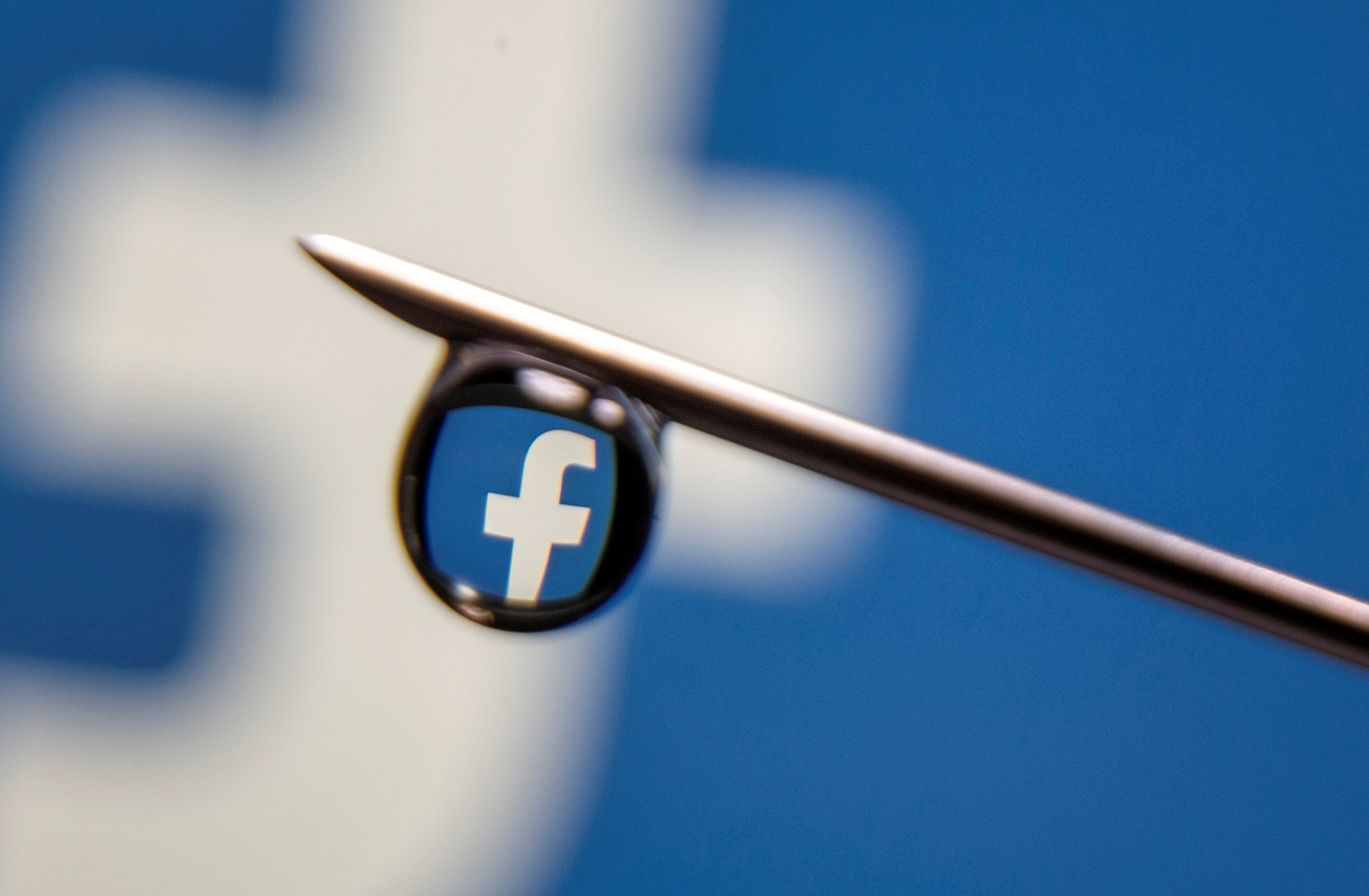 Facebook logo is reflected in a drop on a syringe needle in this illustration photo taken March 16, 2021. REUTERS/Dado Ruvic/Illustration/File Photo