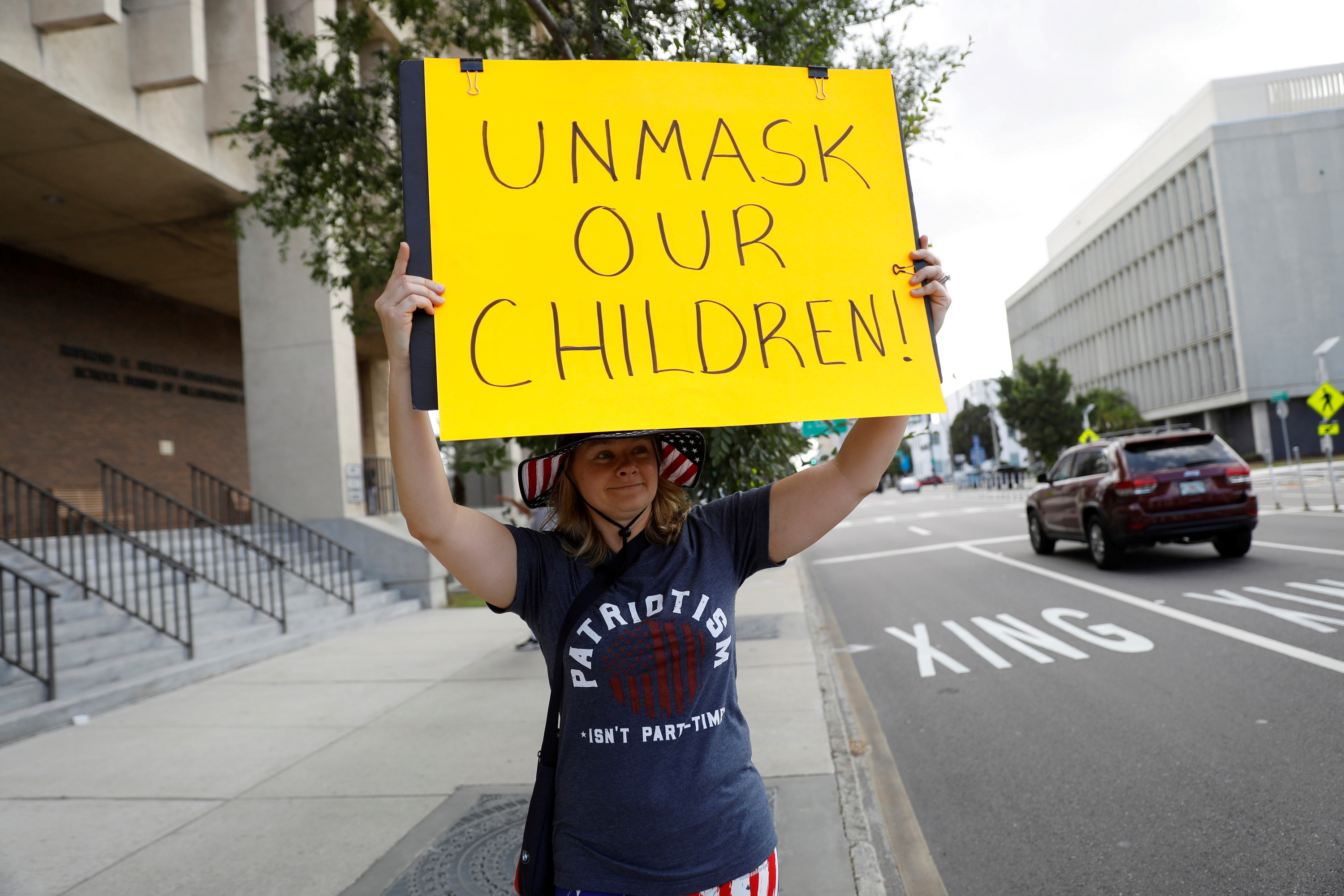 A protester who is against the school mask mandate, enacted to help slow the spread of COVID-19, stands outside with a sign at a Hillsborough County School Board meeting in Tampa, Florida, U.S. May 18, 2021.  REUTERS/Octavio Jones/File Photo