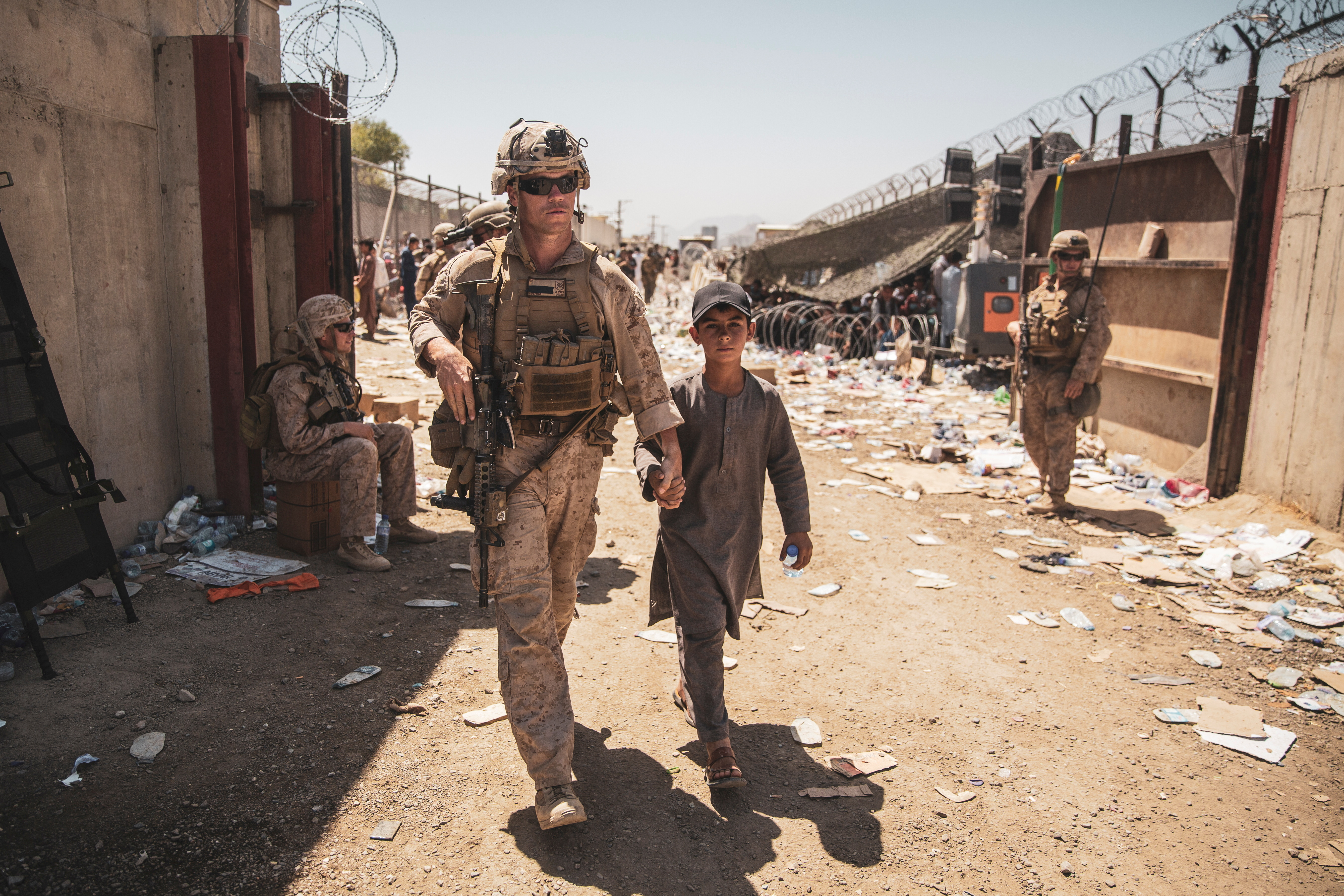A U.S. Marine with the Special Purpose Marine Air-Ground Task Force-Crisis Response-Central Command (SPMAGTF-CR-CC) escorts a child to his family during an evacuation at Hamid Karzai International Airport in Kabul, Afghanistan, August 24, 2021.   Sgt. Samuel Ruiz/U.S. Marine Corps/Handout via REUTERS