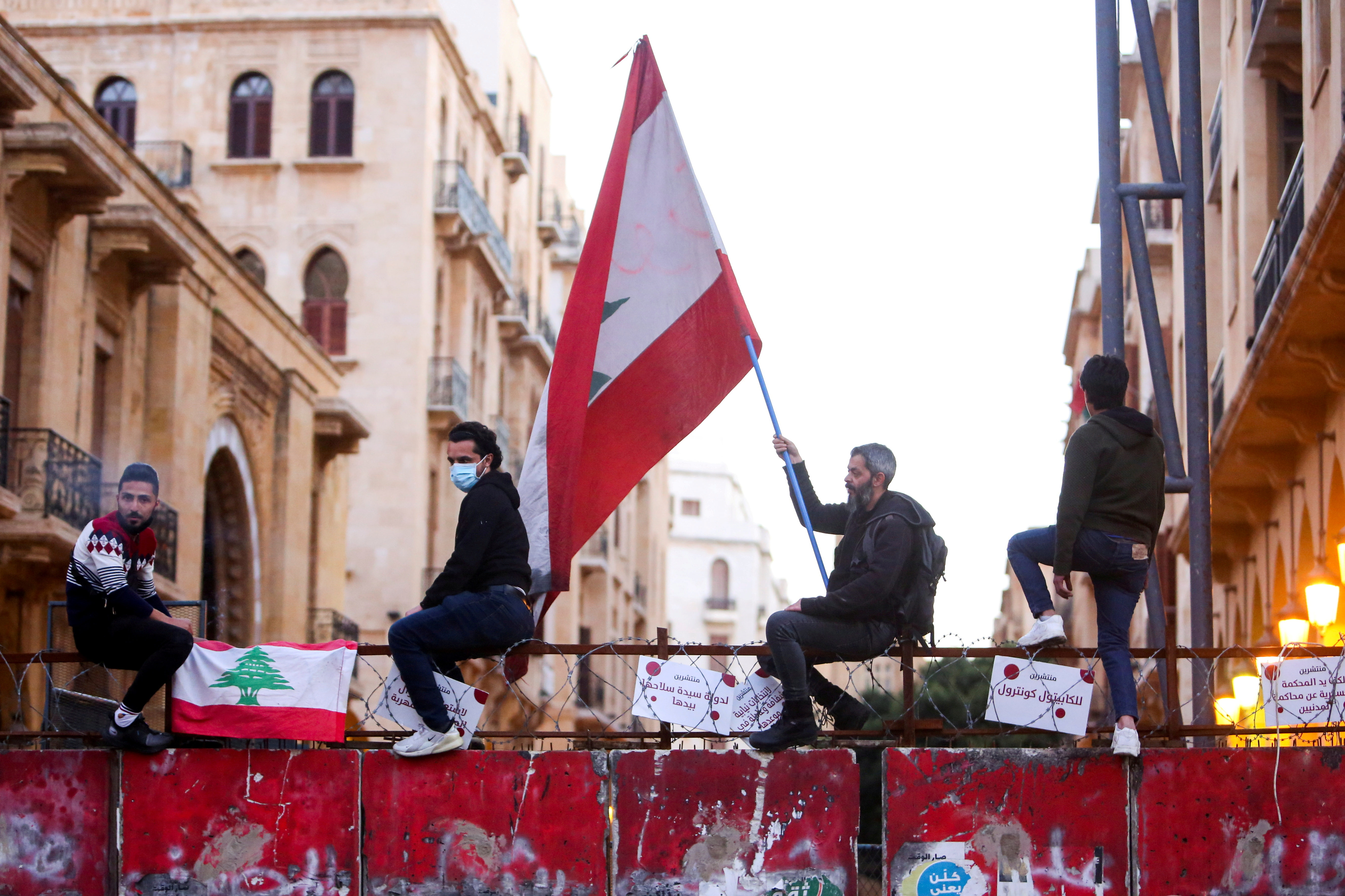 A demonstrator holds a Lebanese flag during a protest against the fall in Lebanese pound currency and mounting economic hardships, in Beirut, Lebanon March 12, 2021. REUTERS/Aziz Taher