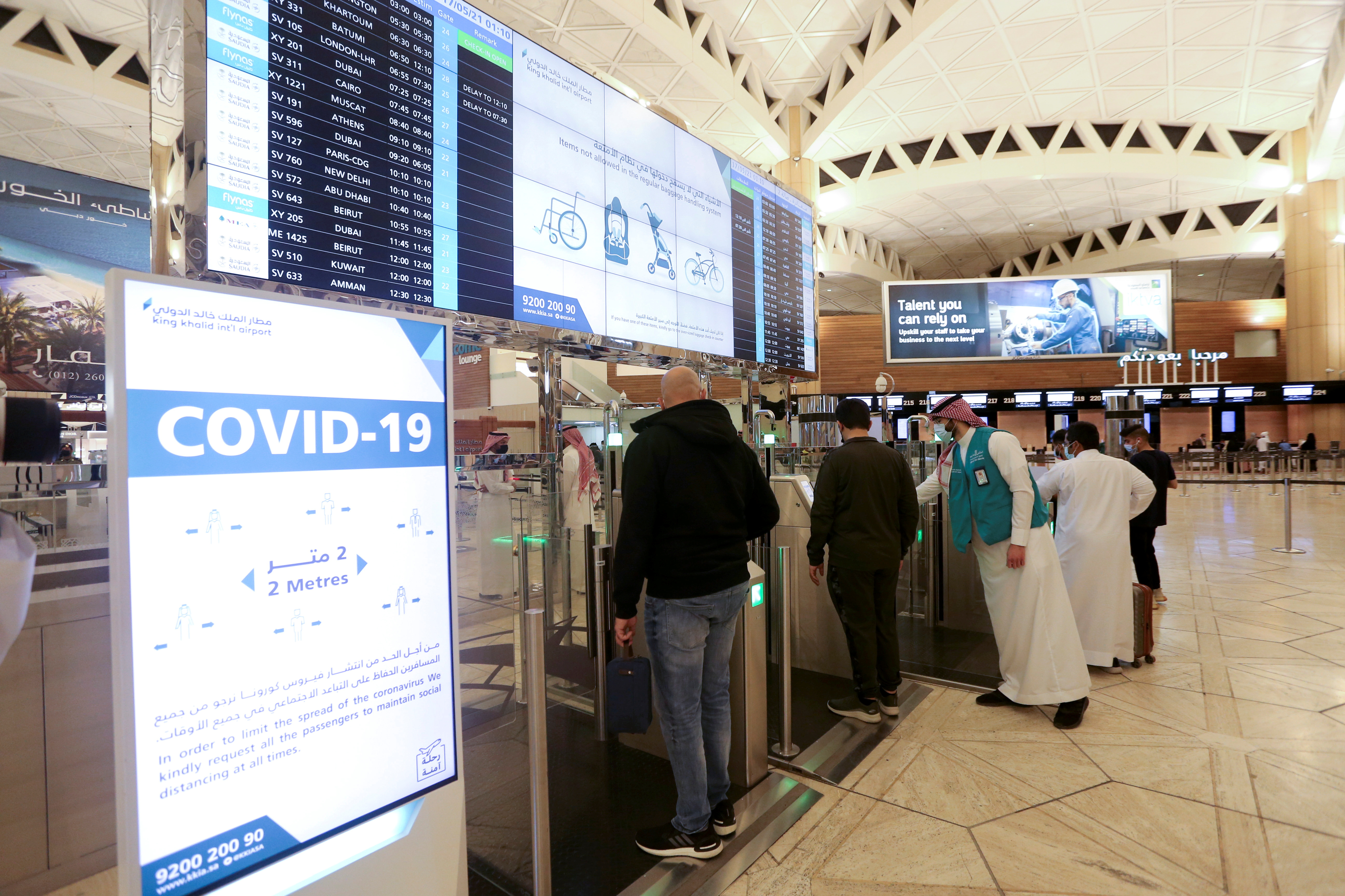 Saudi nationals scan their documents at a digital-Immigration gate at the King Khalid International Airport, after Saudi authorities lifted the travel ban on its citizens after fourteen months due to coronavirus disease (COVID-19) restrictions, in Riyadh, Saudi Arabia, May 16, 2021. REUTERS/Ahmed Yosri