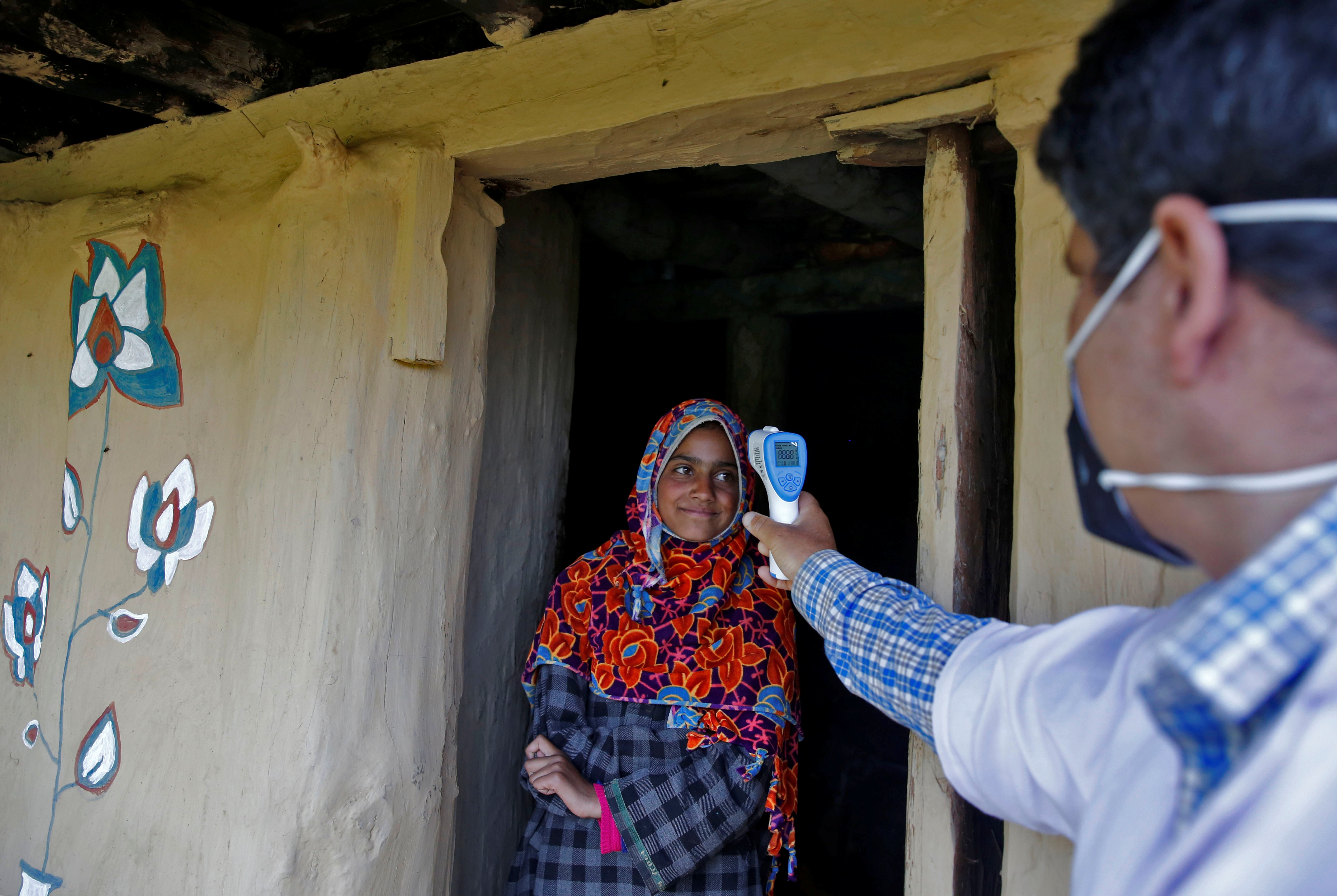 A healthcare worker checks temperature of a shepherd girl at her hut during a COVID-19 vaccination drive at a forest area in south Kashmir's Pulwama district June 7, 2021. REUTERS/Danish Ismail
