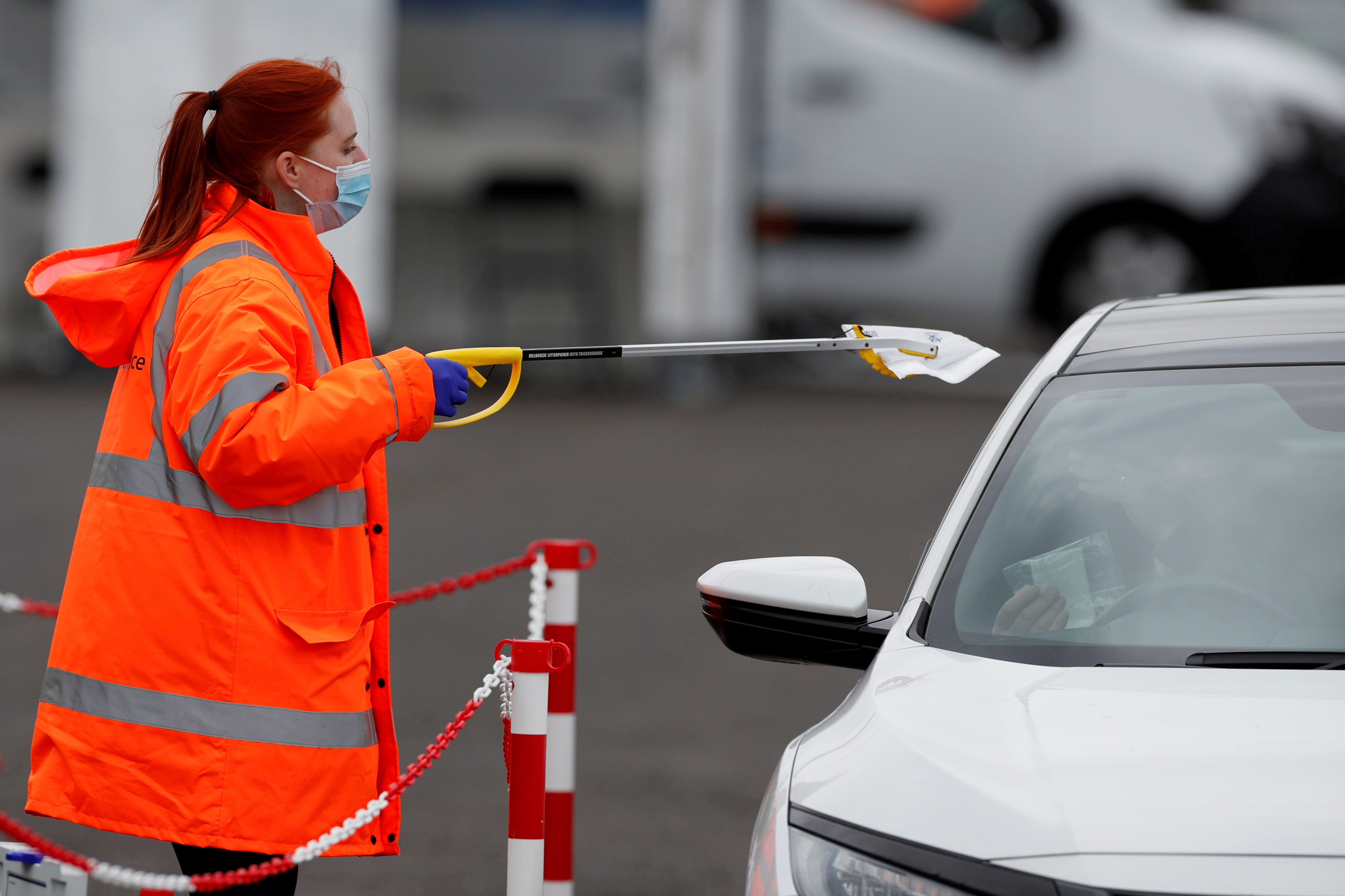 Staff member collects PCR tests for the coronavirus disease (COVID-19) from members of the public, who have done a test in their own car, at a mobile testing unit at Oasis Beach Swimming Pool in Bedford, Britain May 25, 2021. REUTERS/Paul Childs/File Photo