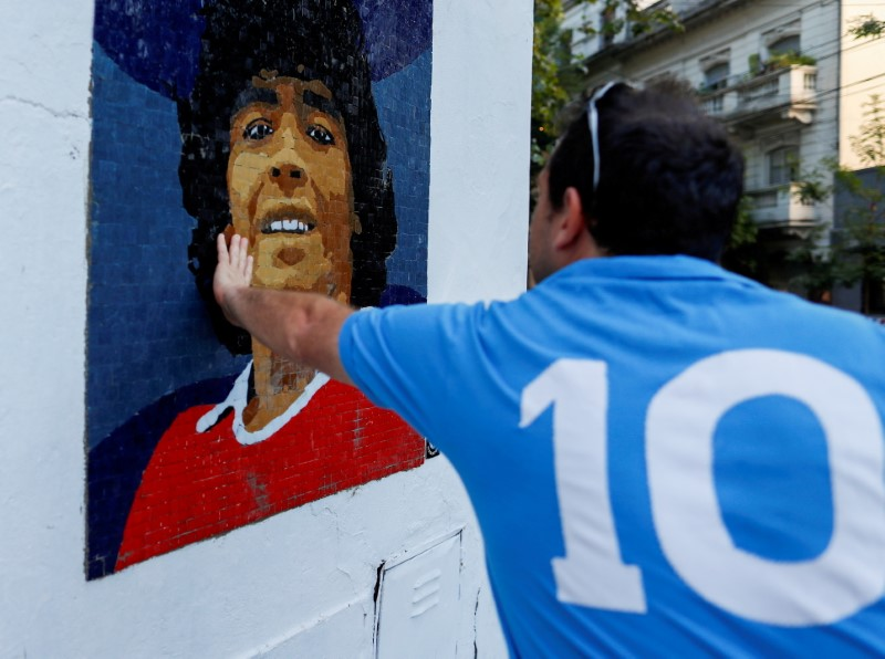 A man touches a mosaic made by the cultural organisation Comando Maradona as a homage to late Argentine soccer superstar Diego Armado Maradona, in Buenos Aires, Argentina February 25, 2021. REUTERS/Agustin Marcarian/File Photo