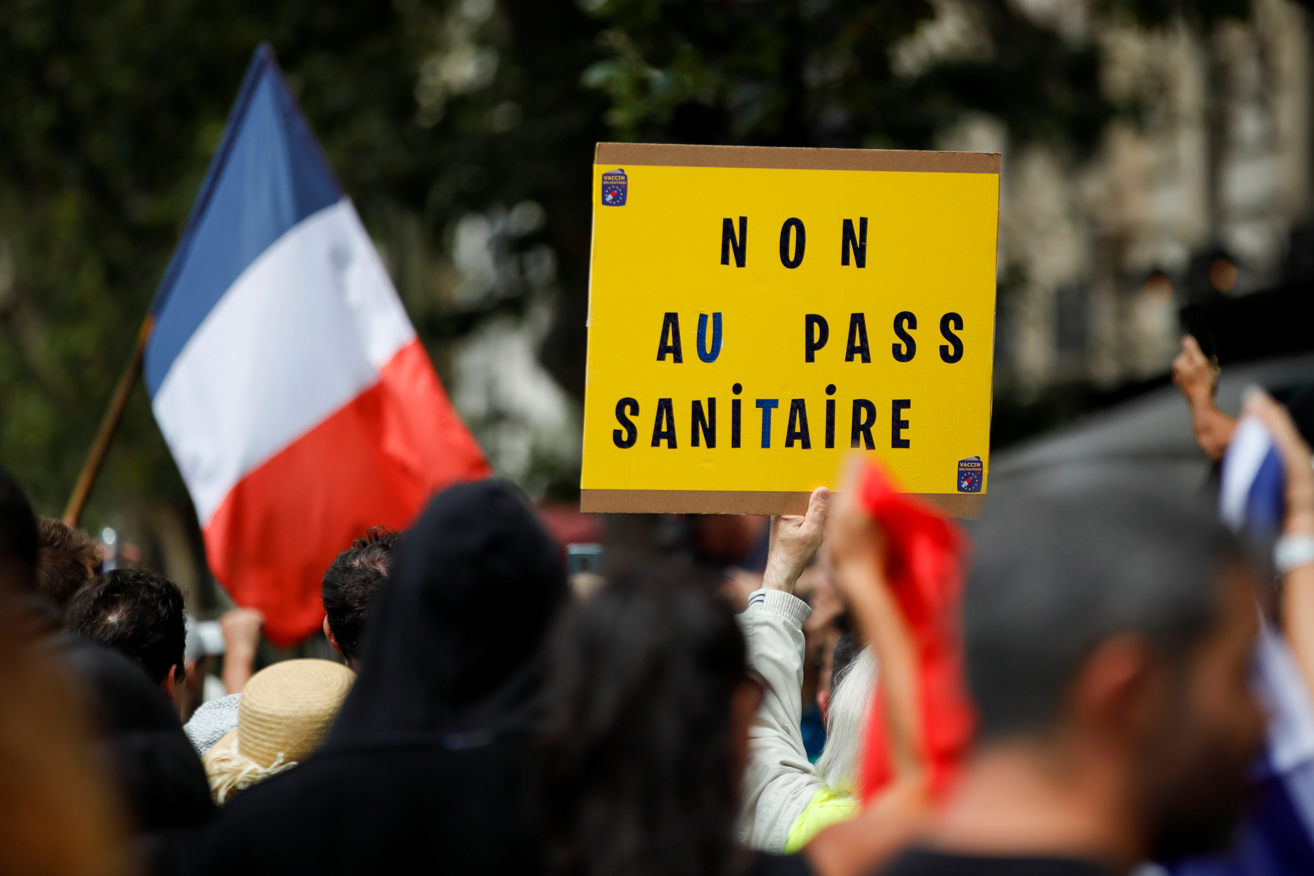 """A protester holds a sign reading """"No to health pass"""" during a demonstration called by the """"yellow vest"""" (gilets jaunes) movement against France's restrictions, including a compulsory health pass, to fight the coronavirus disease (COVID-19) outbreak, in Paris, France, July 31, 2021. REUTERS/Sarah Meyssonnier"""