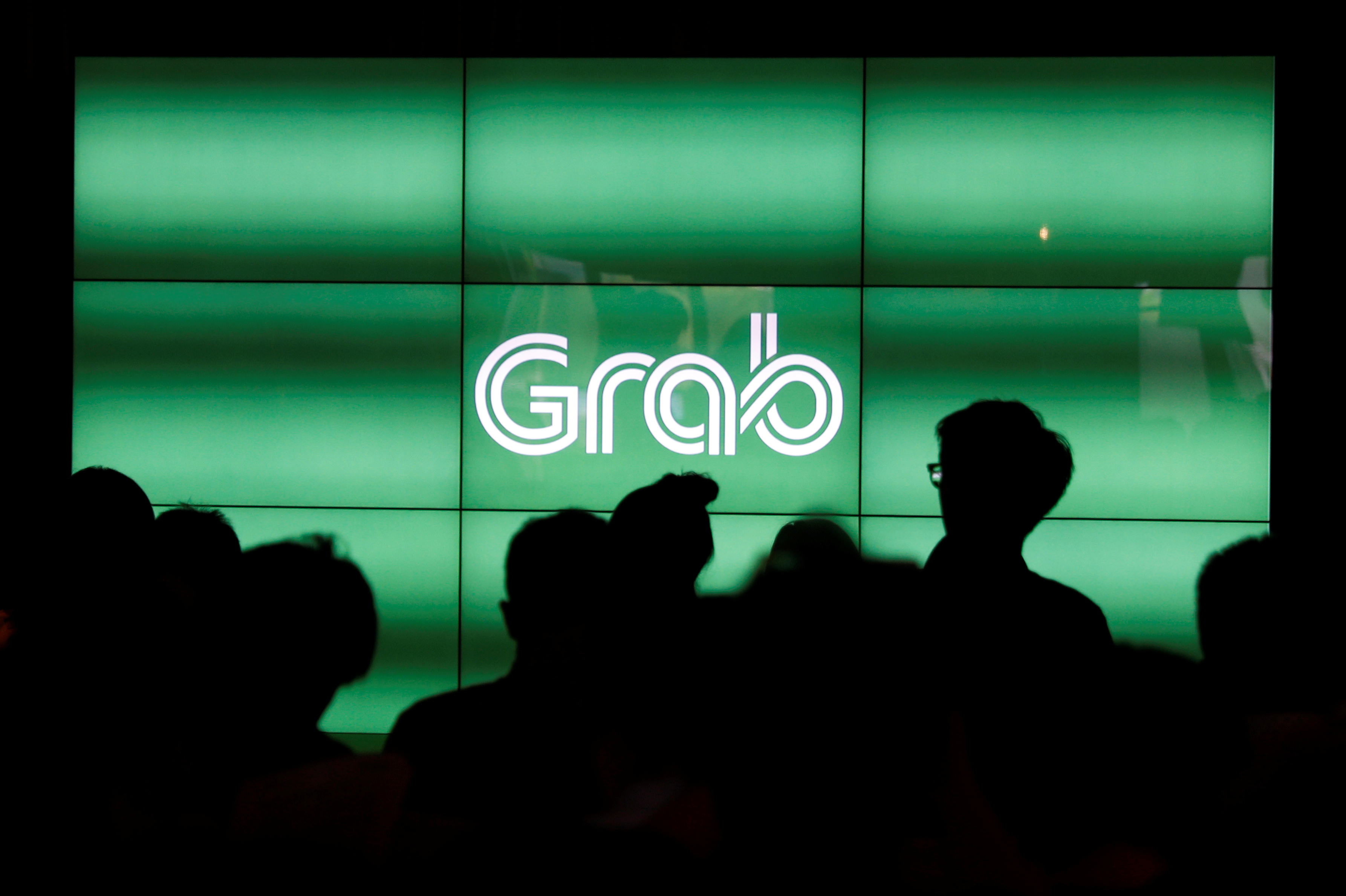 People wait for the start of Grab's fifth anniversary news conference in Singapore June 6, 2017. REUTERS/Edgar Su