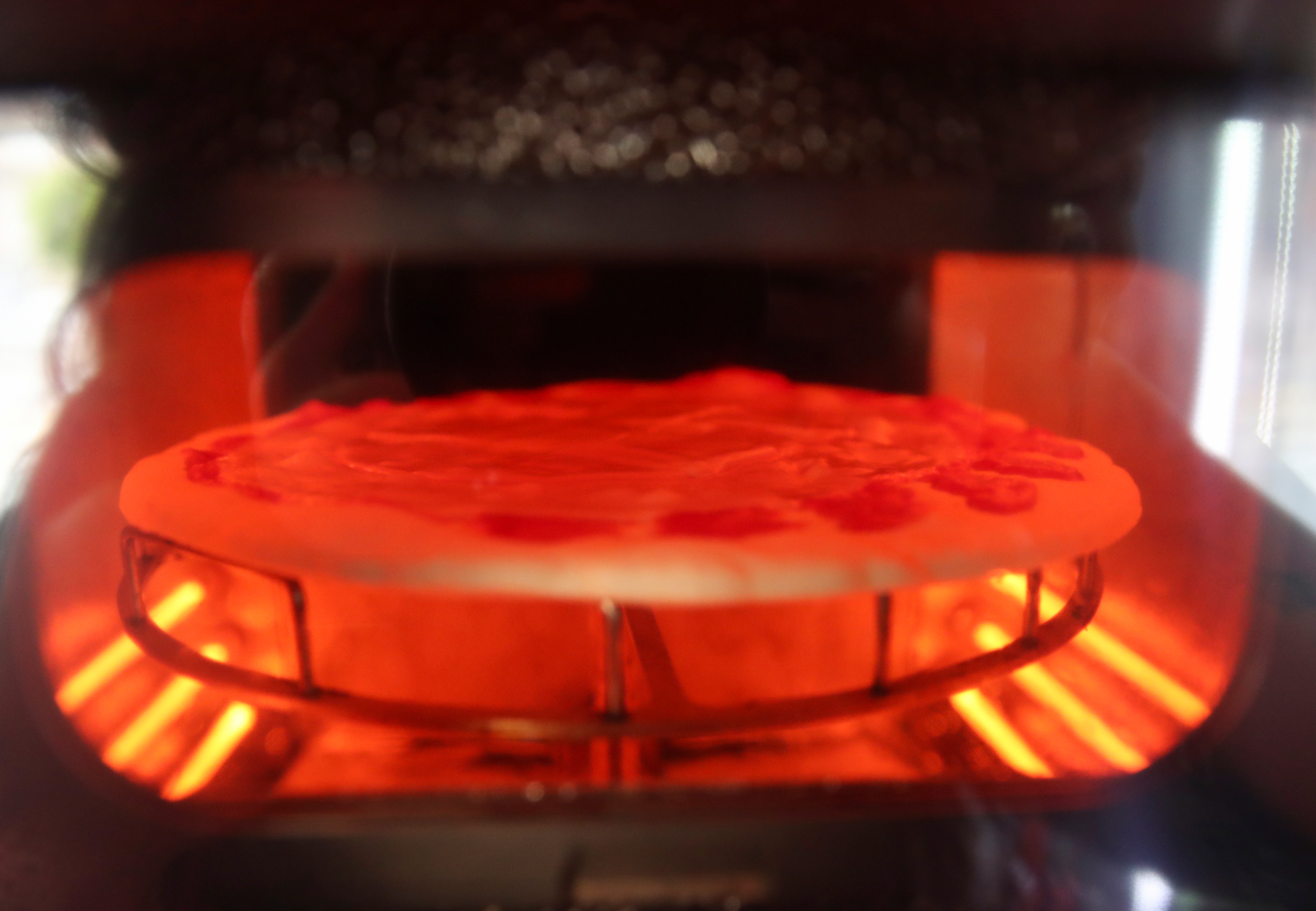 A pizza being baked is seen in the first automatic pizza vending machine, which is capable of kneading, seasoning and cooking the pizza in three minutes, in Rome, Italy, May 6, 2021. REUTERS/Yara Nardi