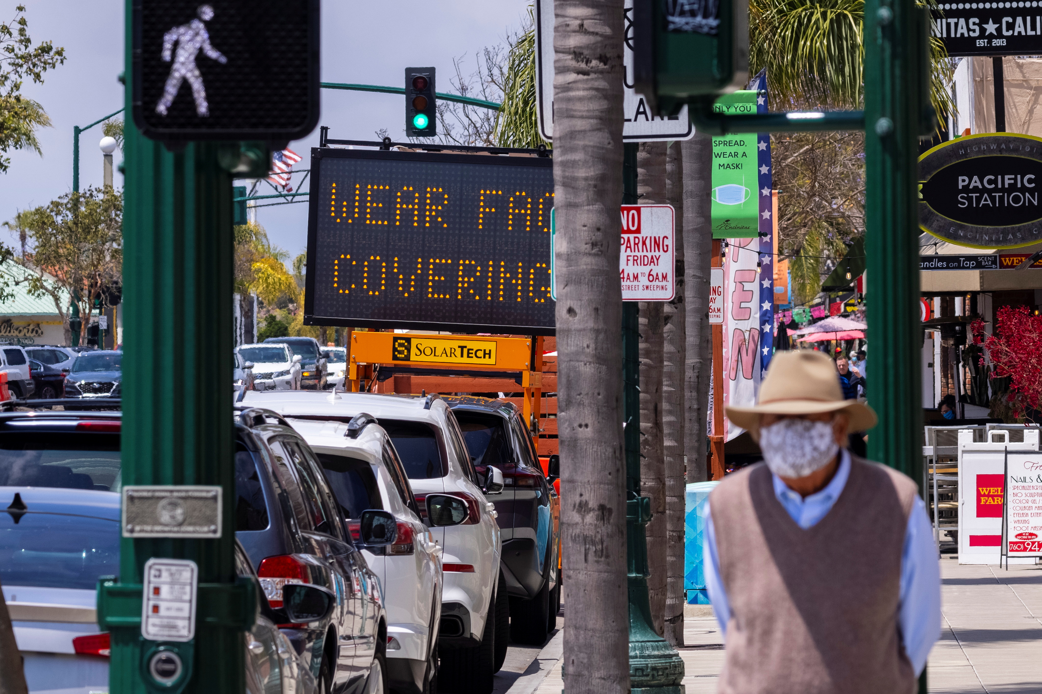 A man walks down a street in Encinitas, as California Governor Gavin Newsom said his state would keep its mask order in place for another month, in California, U.S., May 17, 2021. REUTERS/Mike Blake