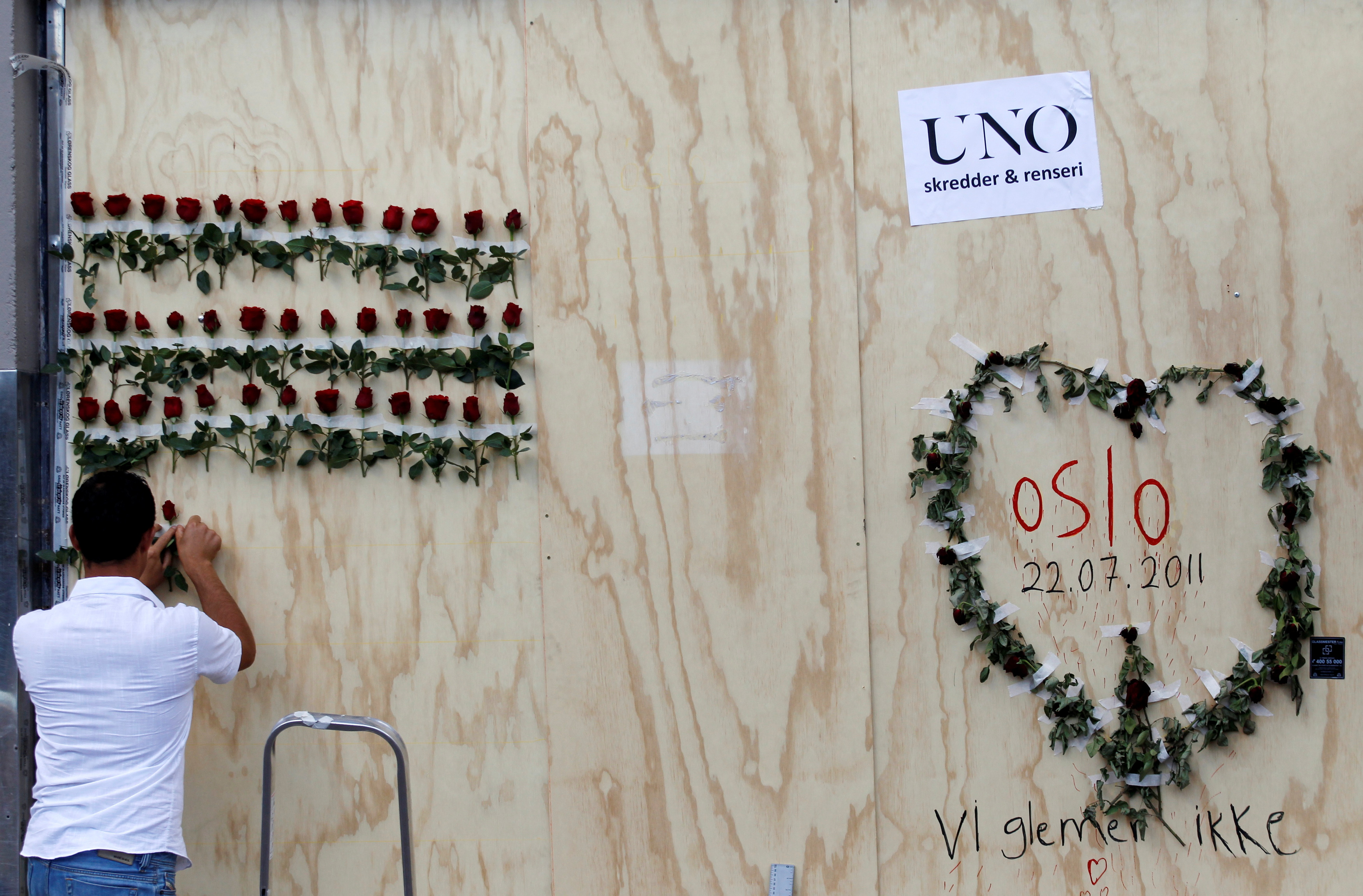 A man arranges flowers next to a graffitti marking a bomb attack last Friday, in the centre of Oslo July 28, 2011. Norwegian police on Thursday ended a six-day search for bodies on the island where anti-Islamist extremist Anders Behring Breivik killed 68 people and say they are increasingly certain he acted alone. Breivik, 32, killed a total of 76 people in a bomb attack in central Oslo followed by the shooting rampage at the island summer camp for the ruling Labour Party's youth wing. REUTERS/Stoyan Nenov/File Photo