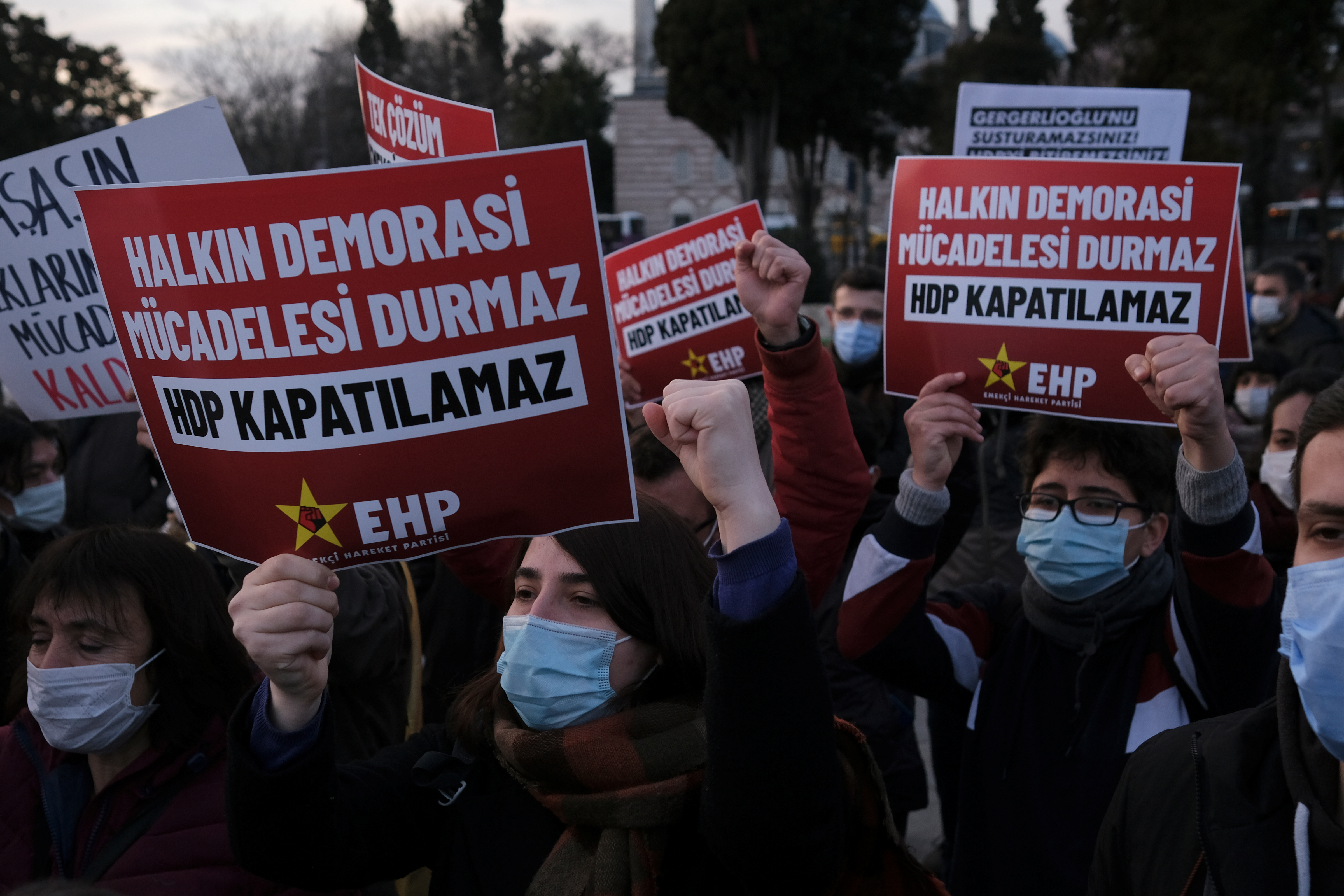 People shout slogans during a demonstration to protest against the court case launched for closure of the pro-Kurdish opposition Peoples' Democratic Party (HDP) in Istanbul, Turkey March 18, 2021. Placards read: