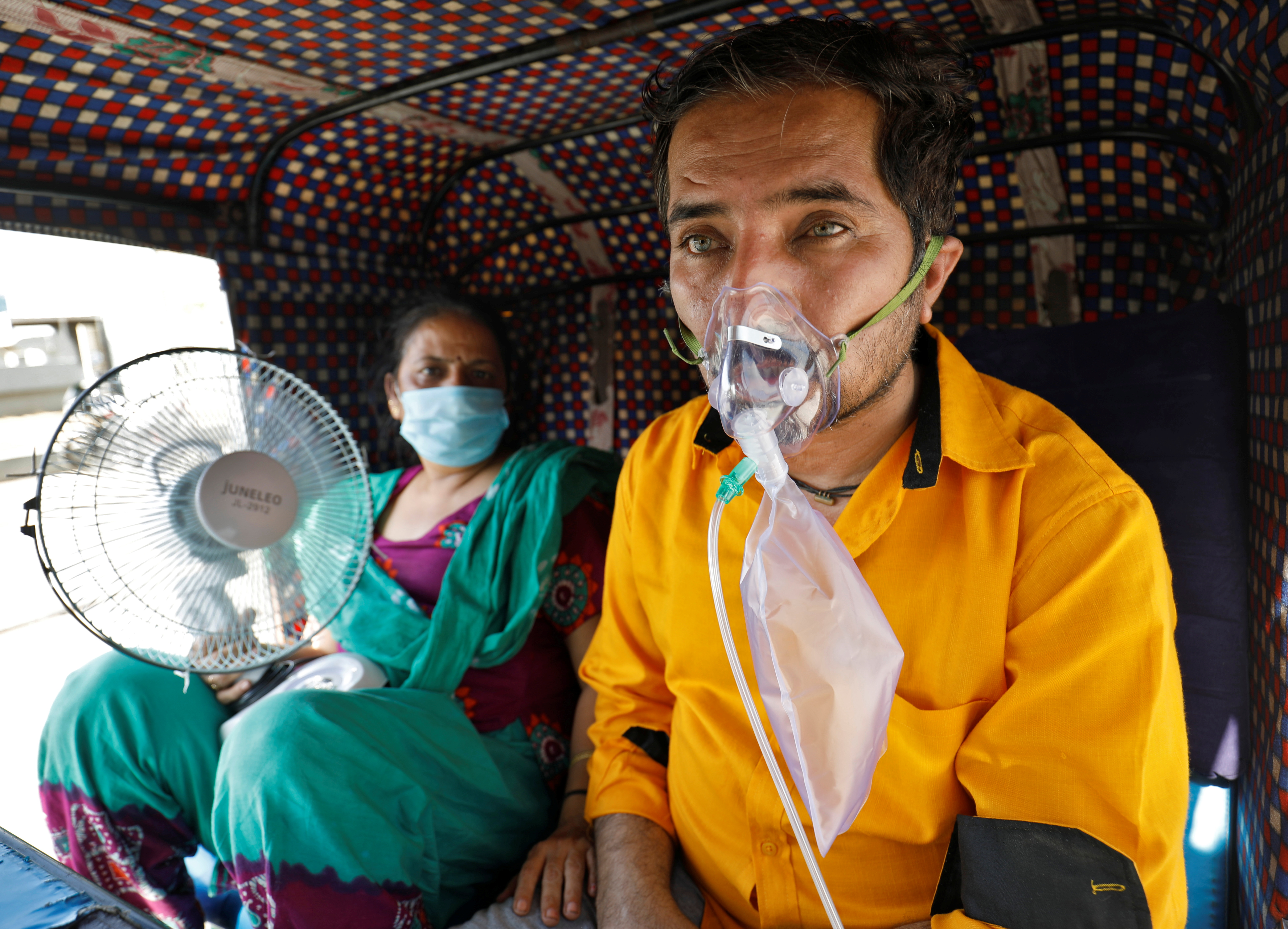 A patient wearing an oxygen mask looks on as his wife holds a battery-operated fan while waiting inside an auto-rickshaw to enter a COVID-19 hospital for treatment, amidst the spread of the coronavirus disease (COVID-19) in Ahmedabad, India, April 25, 2021. REUTERS/Amit Dave