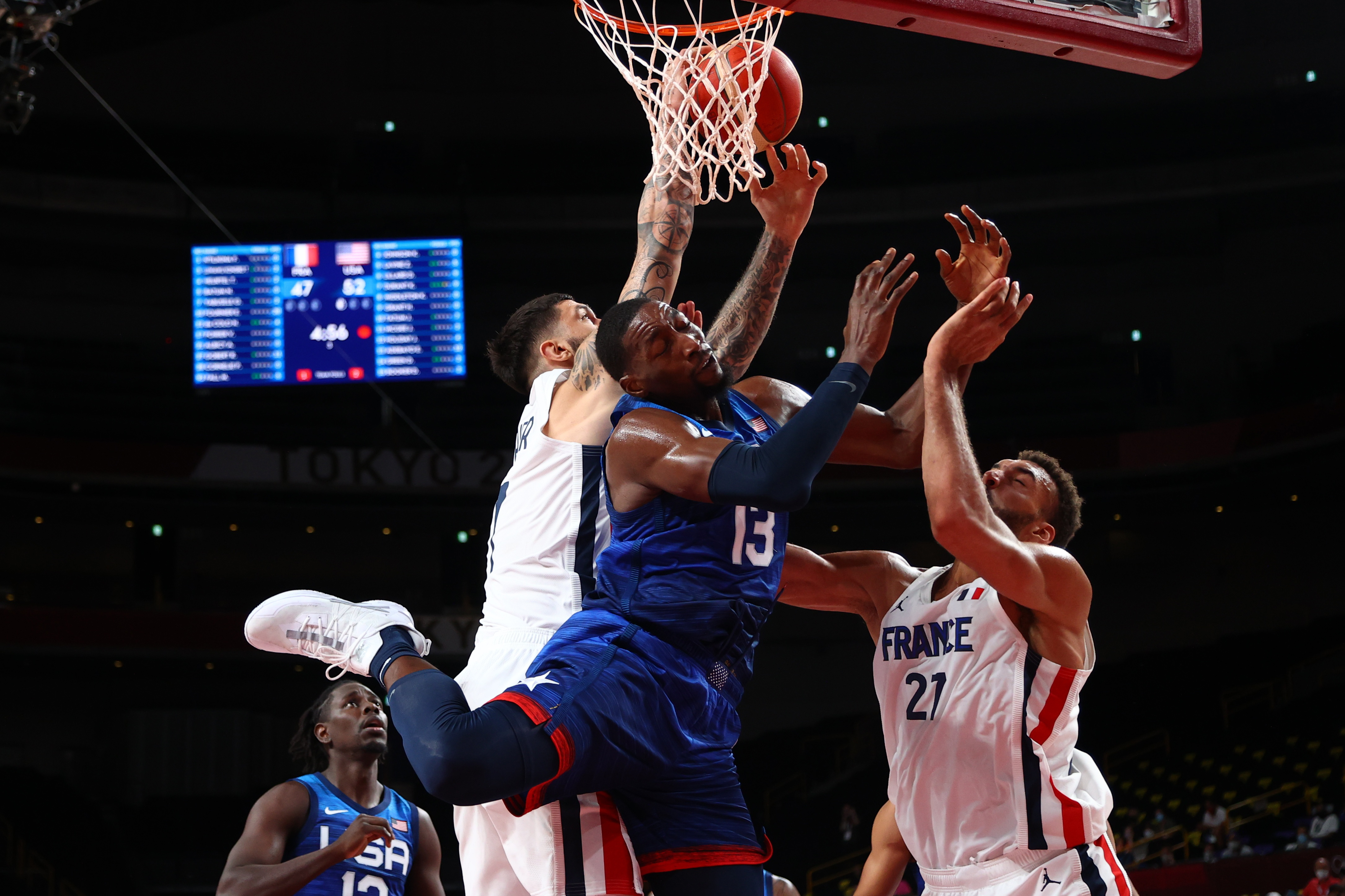 Tokyo 2020 Olympics - Basketball - Men - Group A - France v United States - Saitama Super Arena, Saitama, Japan - July 25, 2021. Edrice Adebayo of the United States in action at the rim with Rudy Gobert of France and Vincent Poirier of France REUTERS/Brian Snyder