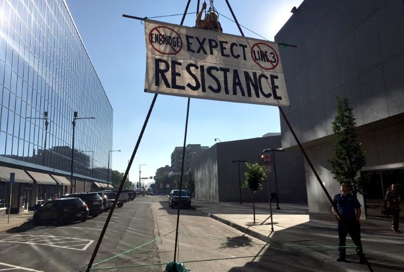 An activist opposing the Enbridge Line 3 oil pipeline dangles from a structure in St. Paul, Minnesota, U.S., June 28, 2018.  REUTERS/Rod Nickel