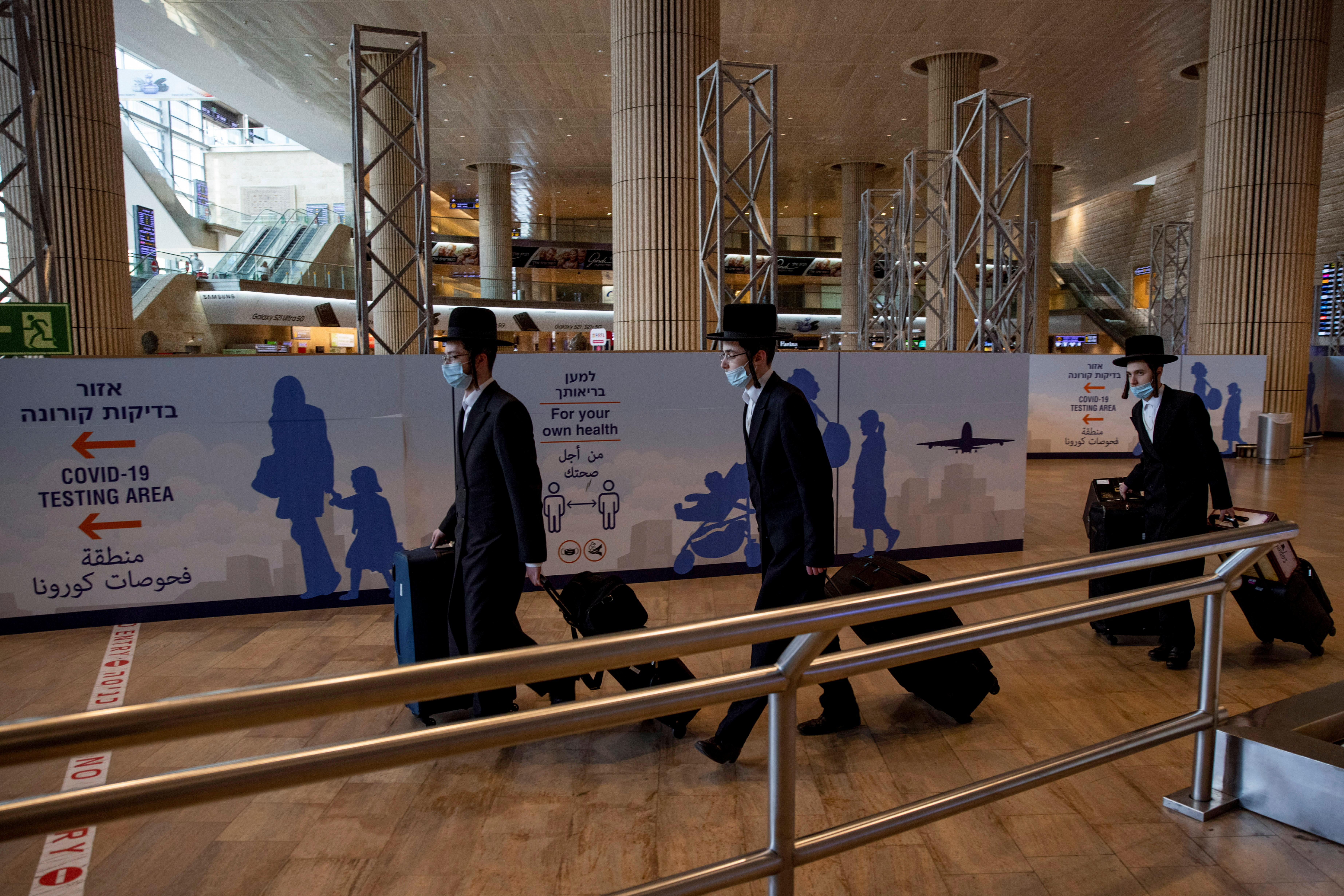 Ultra-Orthodox Jewish men walk after returning from overseas, at Ben Gurion International Airport in Lod, near Tel Aviv, Israel April 13, 2021. REUTERS/Ronen Zvulun