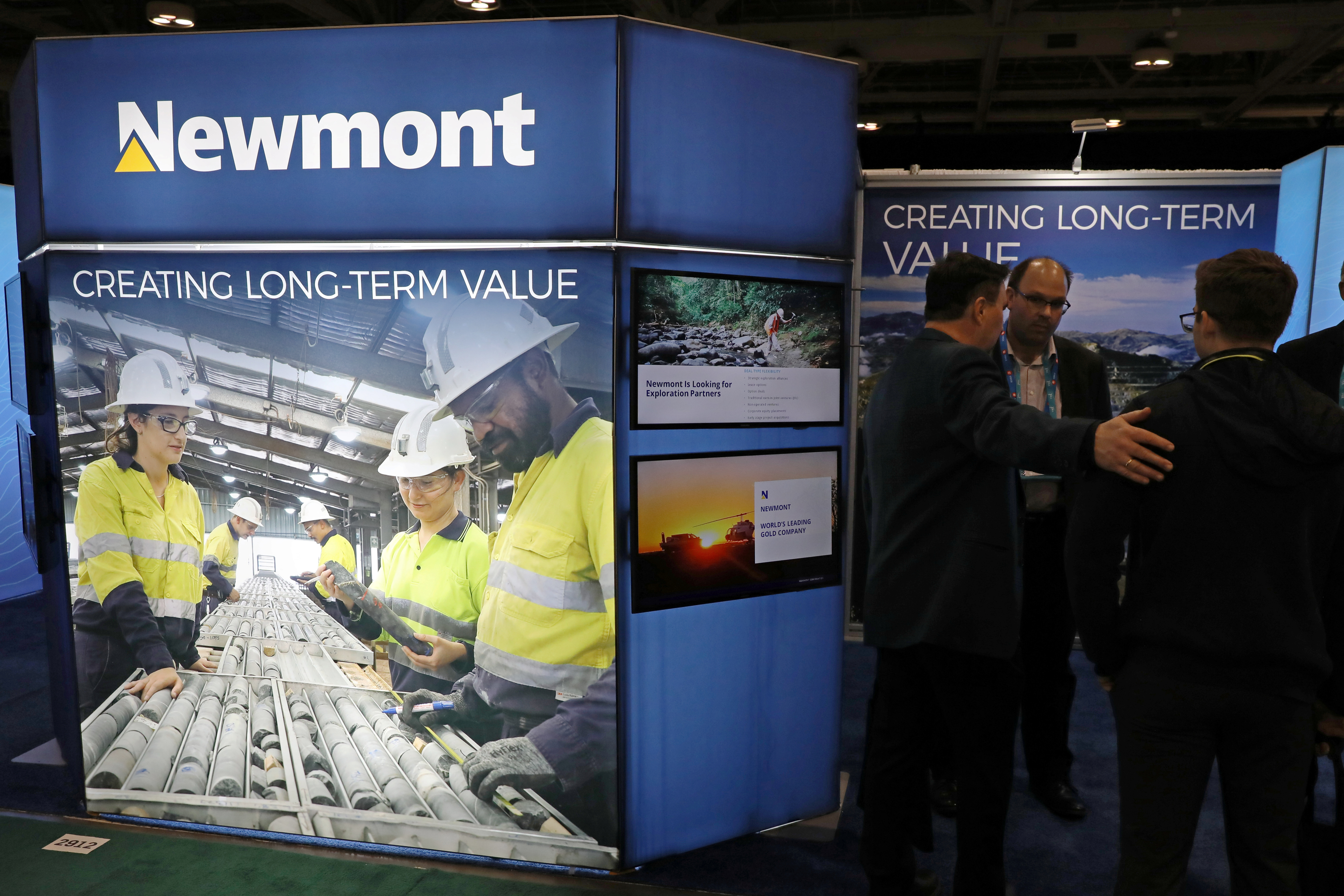 Visitors speak with a representative at the Newmont Corp booth at the Prospectors and Developers Association of Canada (PDAC) annual conference in Toronto, Ontario, Canada March 1, 2020.  REUTERS/Chris Helgren
