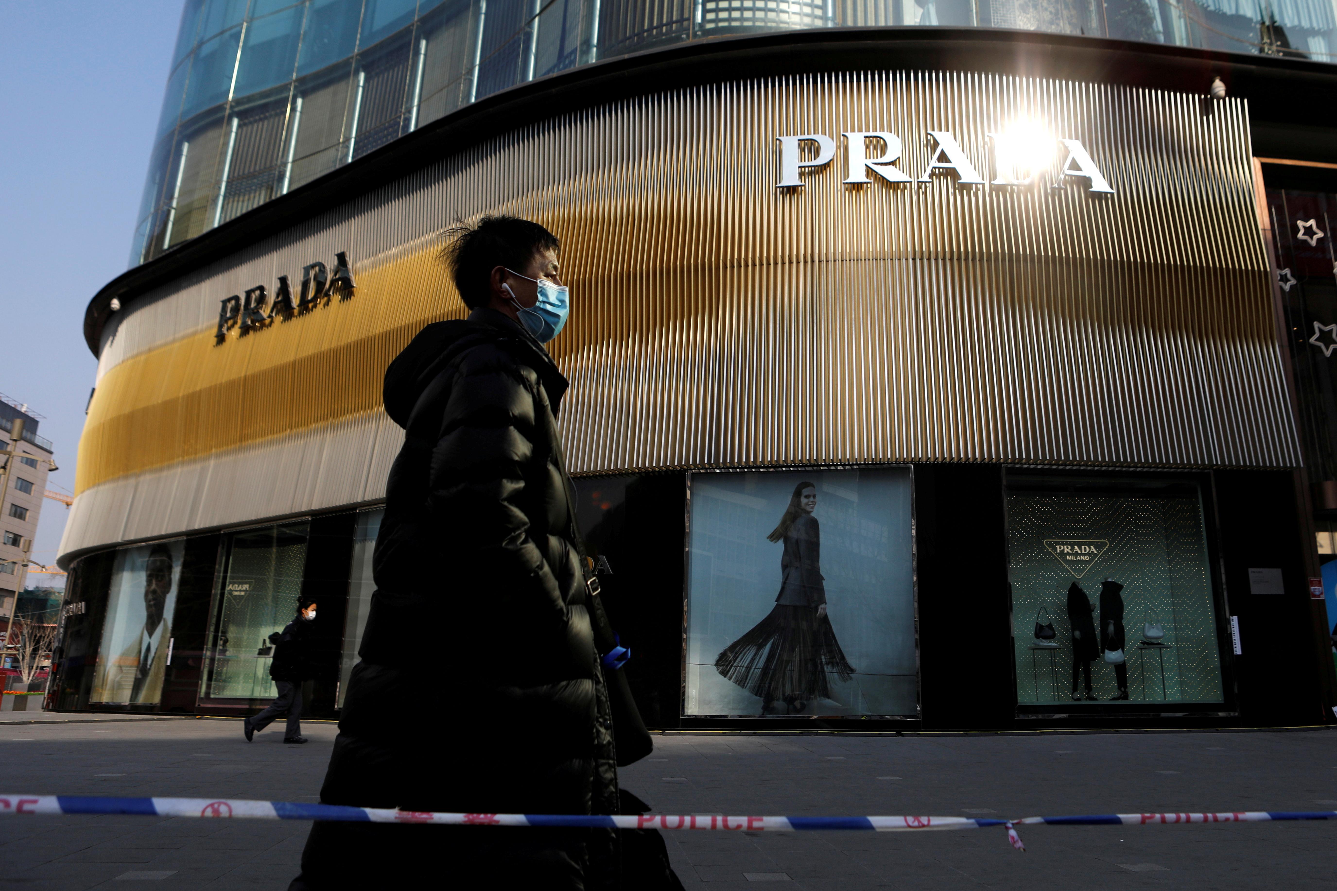 A man wearing a face mask following the coronavirus disease (COVID-19) outbreak walks past a store of Italian luxury brand Prada on a shopping street in Beijing, China, January 20, 2021. REUTERS/Tingshu Wang
