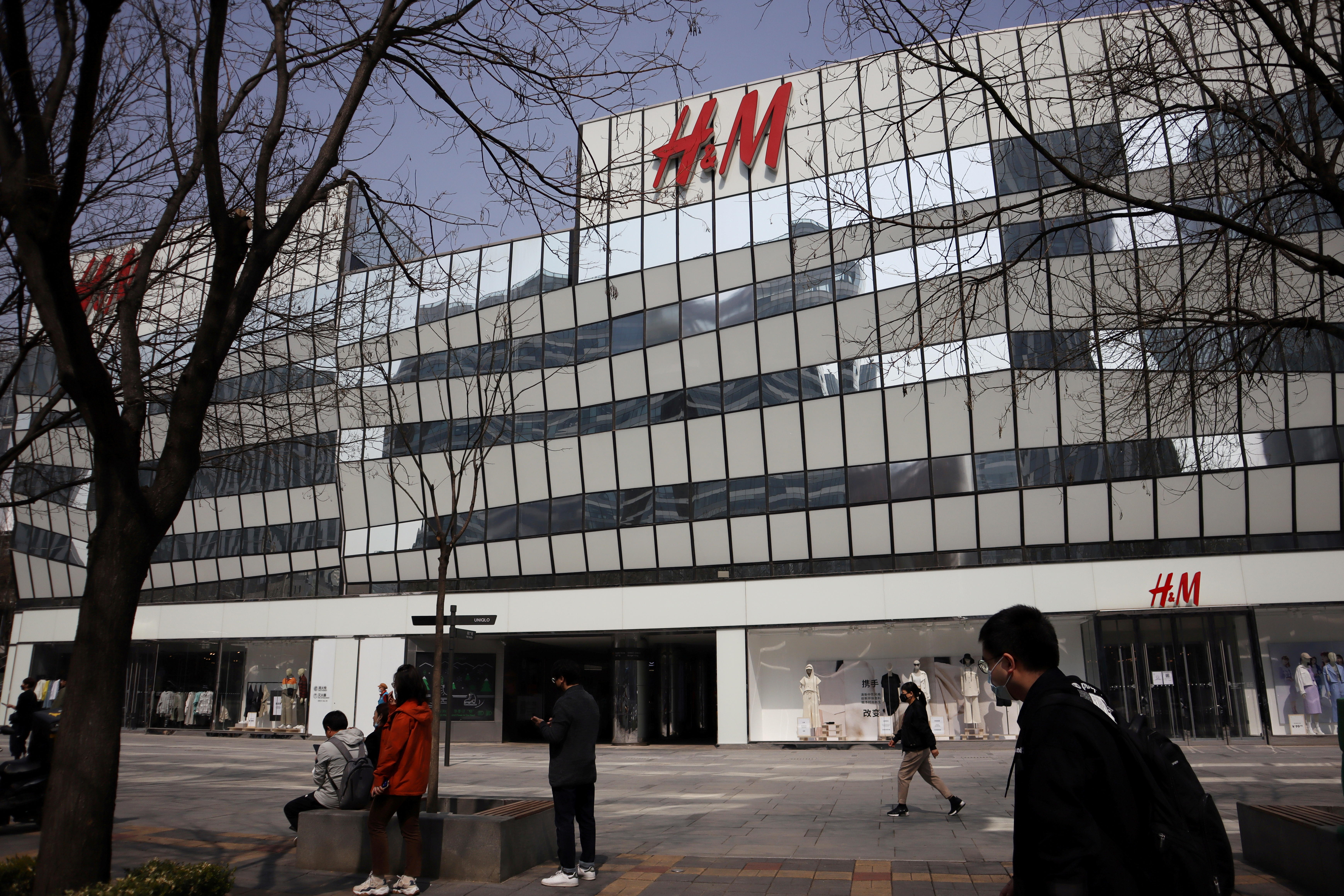 People walk past a store of the Swedish fashion retailer H&M at a shopping complex in Beijing, China March 25, 2021. REUTERS/Florence Lo/File Photo