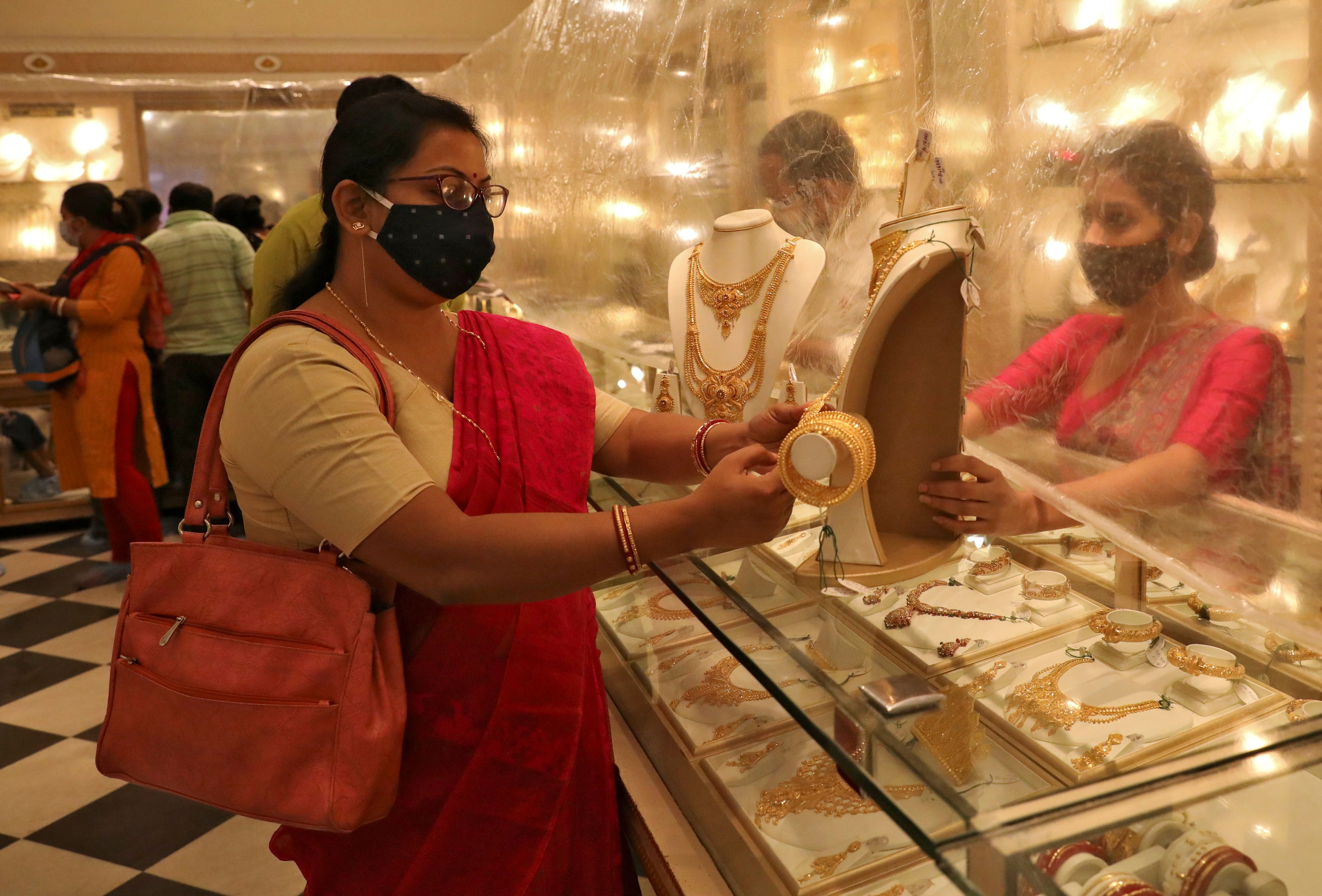 Woman looks at a gold necklace at a jewellery showroom during Dhanteras, a Hindu festival associated with Lakshmi, the goddess of wealth, amidst the spread of COVID-19 in Kolkata, India, November 13, 2020. REUTERS/Rupak De Chowdhuri/File Photo