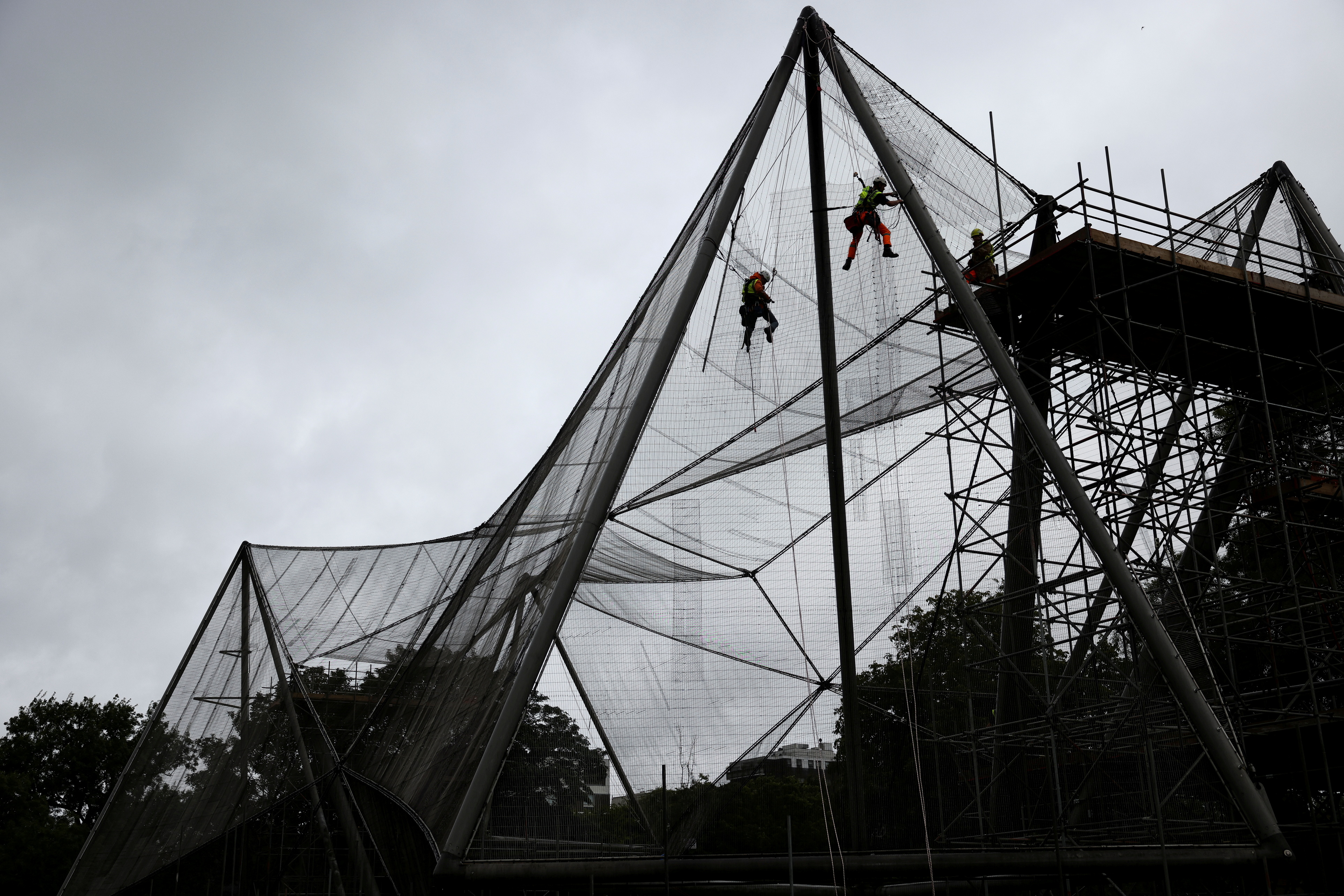 Workers abseil down the Grade II listed Snowdon Aviary at the ZSL London Zoo, to remove the 200 steel mesh panels that wrap around the structure which has stood unchanged for 50 years, as part of a restoration project that will see the aviary transformed in to a new home for a troop of eastern black and white colobus monkeys, in London, Britain, July 30, 2021. REUTERS/Henry Nicholls/File Photo