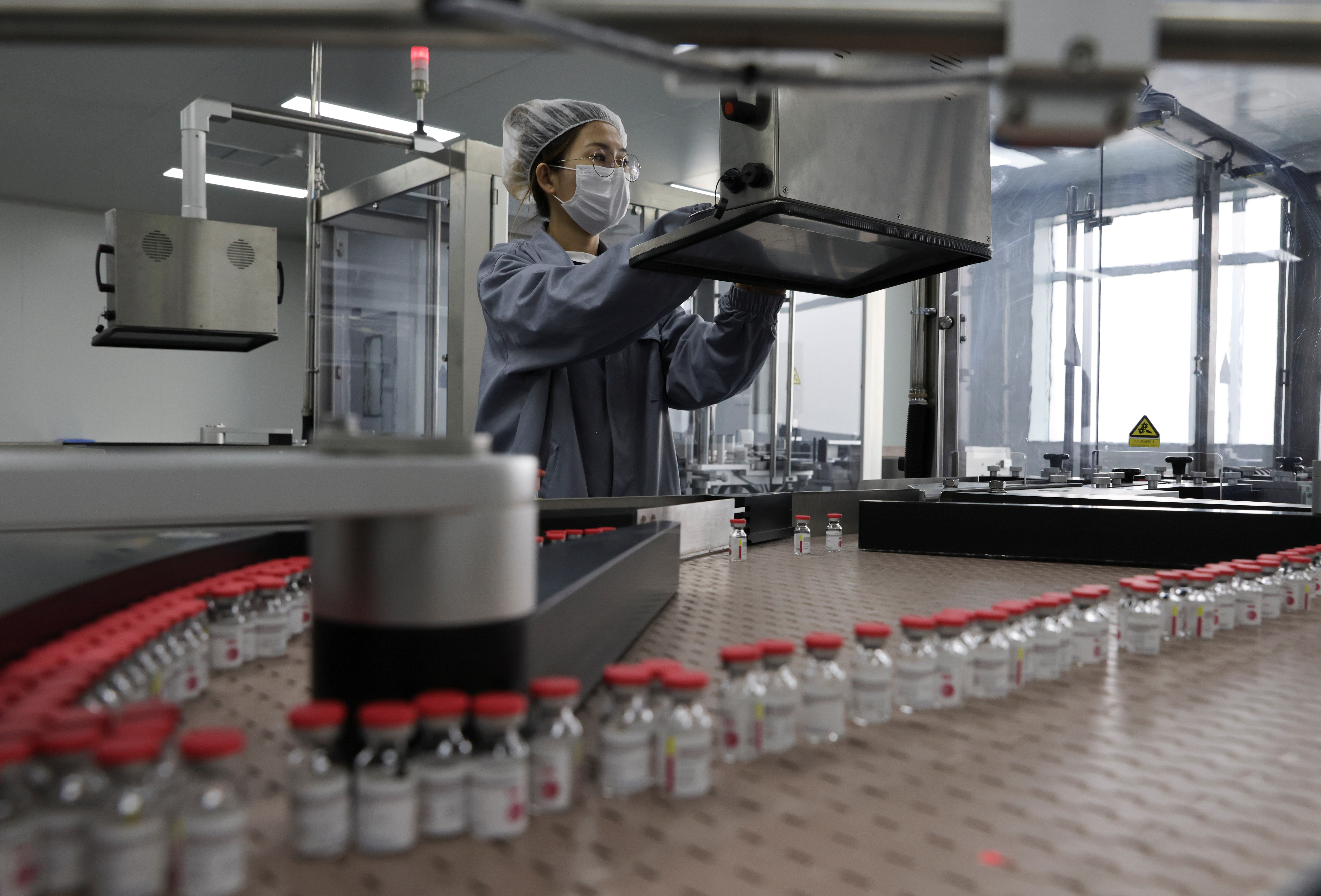 An employee works on the production line of CanSino Biologics Inc's single-dose vaccine against the coronavirus disease (COVID-19) in Tianjin, China April 25, 2021. Picture taken April 25, 2021. China Daily via REUTERS  .