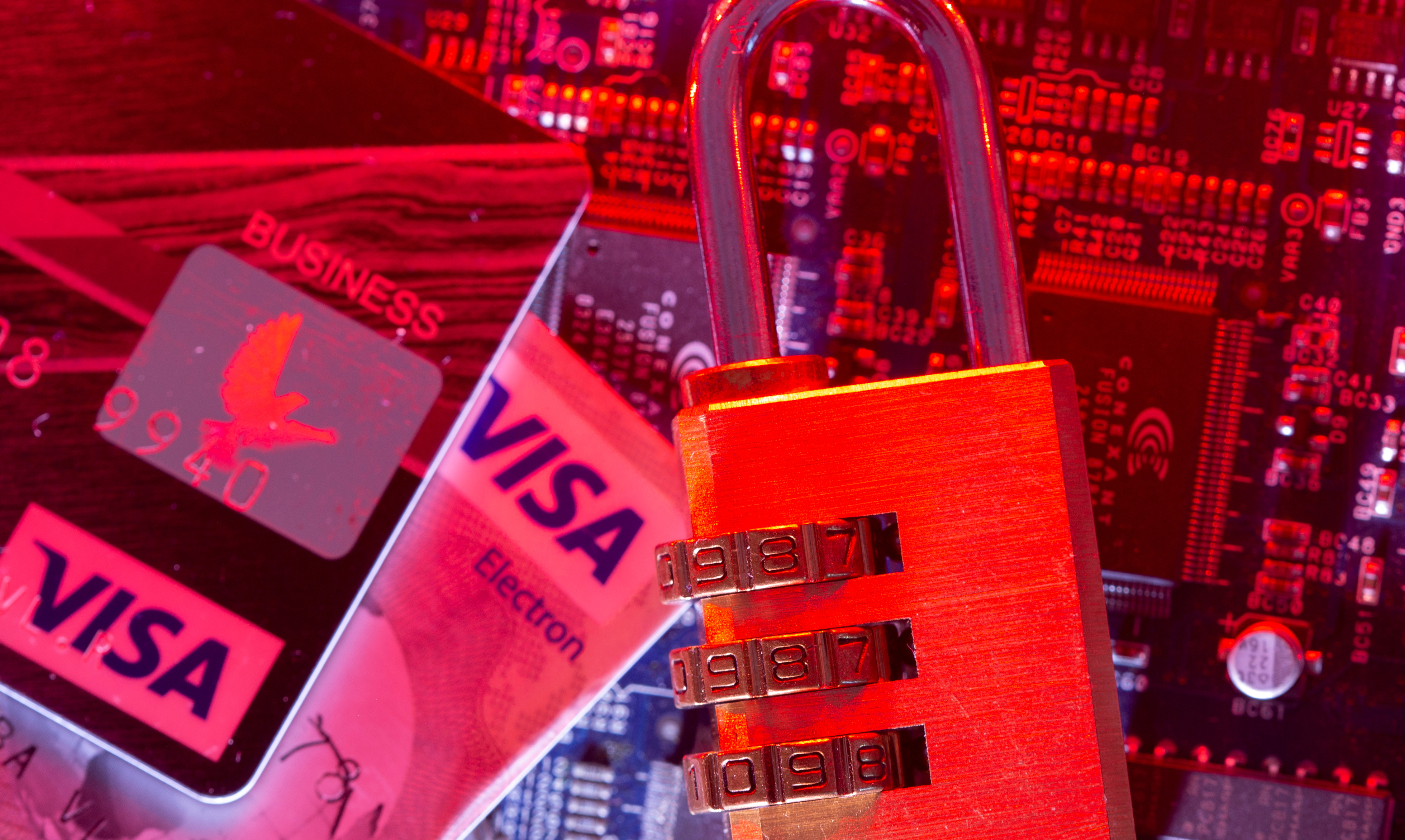 Visa credit cards and a padlock are seen placed on a computer motherboard in this illustration picture taken May 4, 2021. REUTERS/Dado Ruvic/Illustration