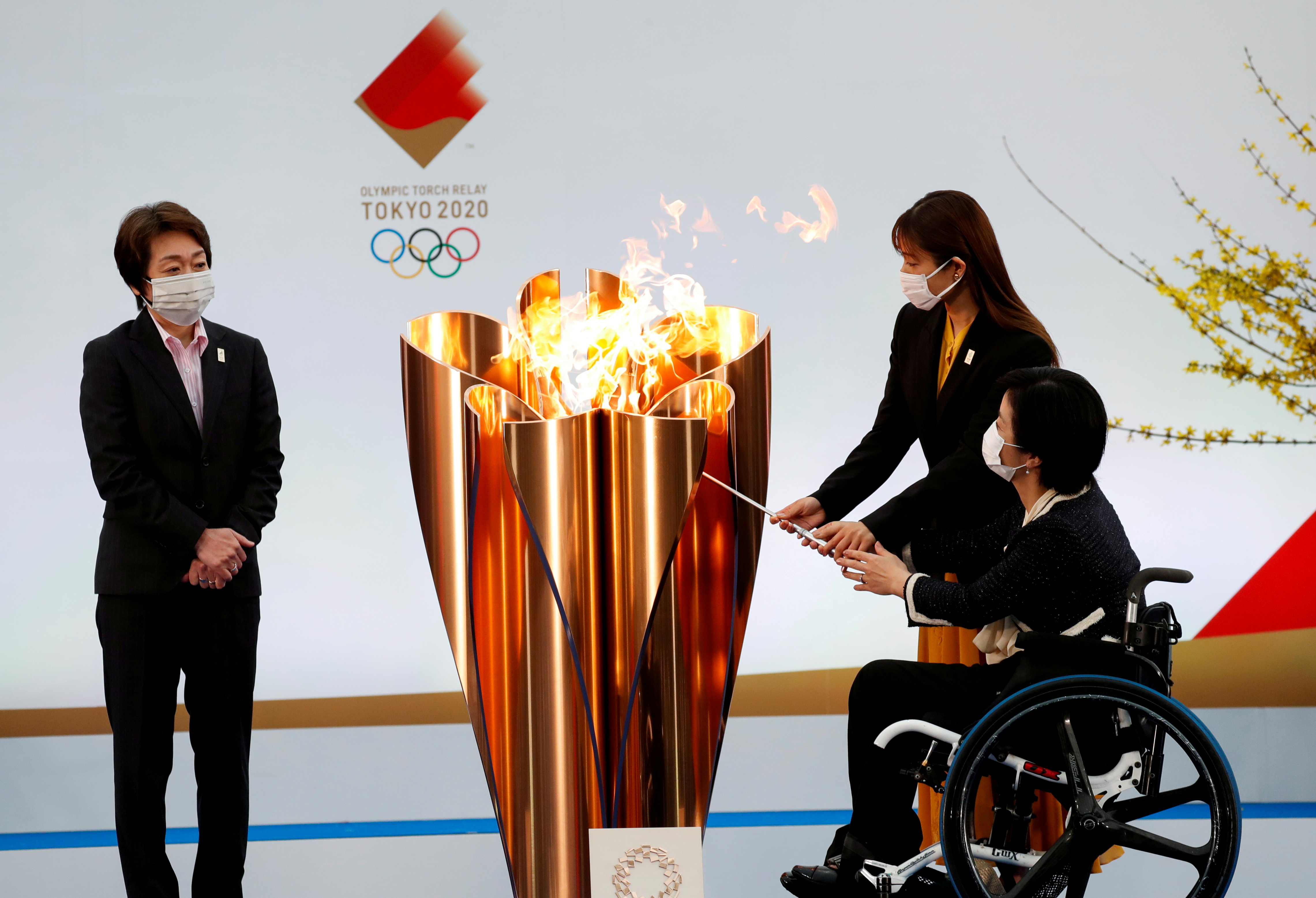 Tokyo 2020 President Seiko Hashimoto looks on as actor Satomi Ishihara and Paralympian Aki Taguchi light the celebration cauldron on the first day of the Tokyo 2020 Olympic torch relay in Naraha, Fukushima prefecture, Japan March 25, 2021. REUTERS/Kim Kyung-Hoon/Pool/File Photo