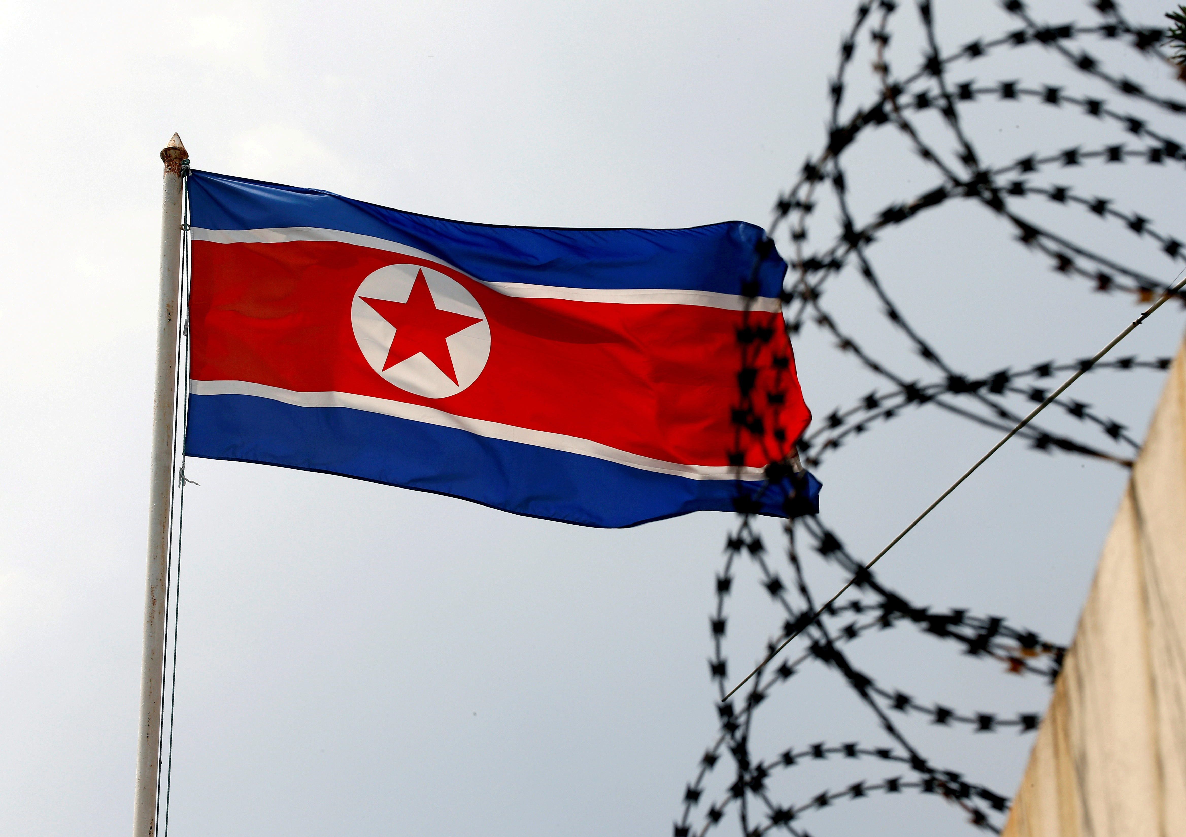 A North Korea flag flutters next to concertina wire at the North Korean embassy in Kuala Lumpur, Malaysia March 9, 2017. REUTERS/Edgar Su/File Photo