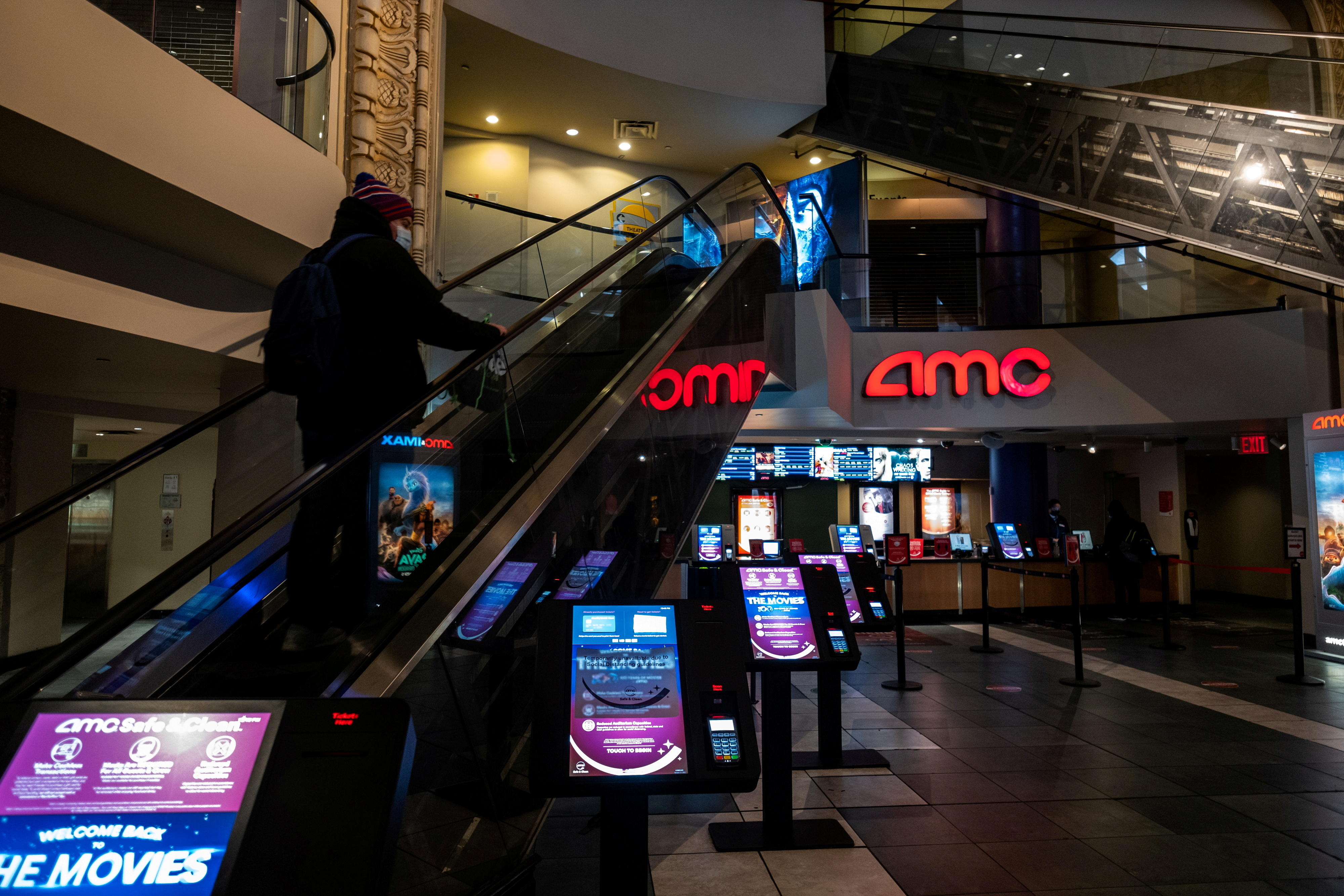 A person wearing a protective mask rides an escalator at the AMC movie theatre in Times Square in the Manhattan borough of New York City, New York, U.S., March 6, 2021. REUTERS/Jeenah Moon/File Photo