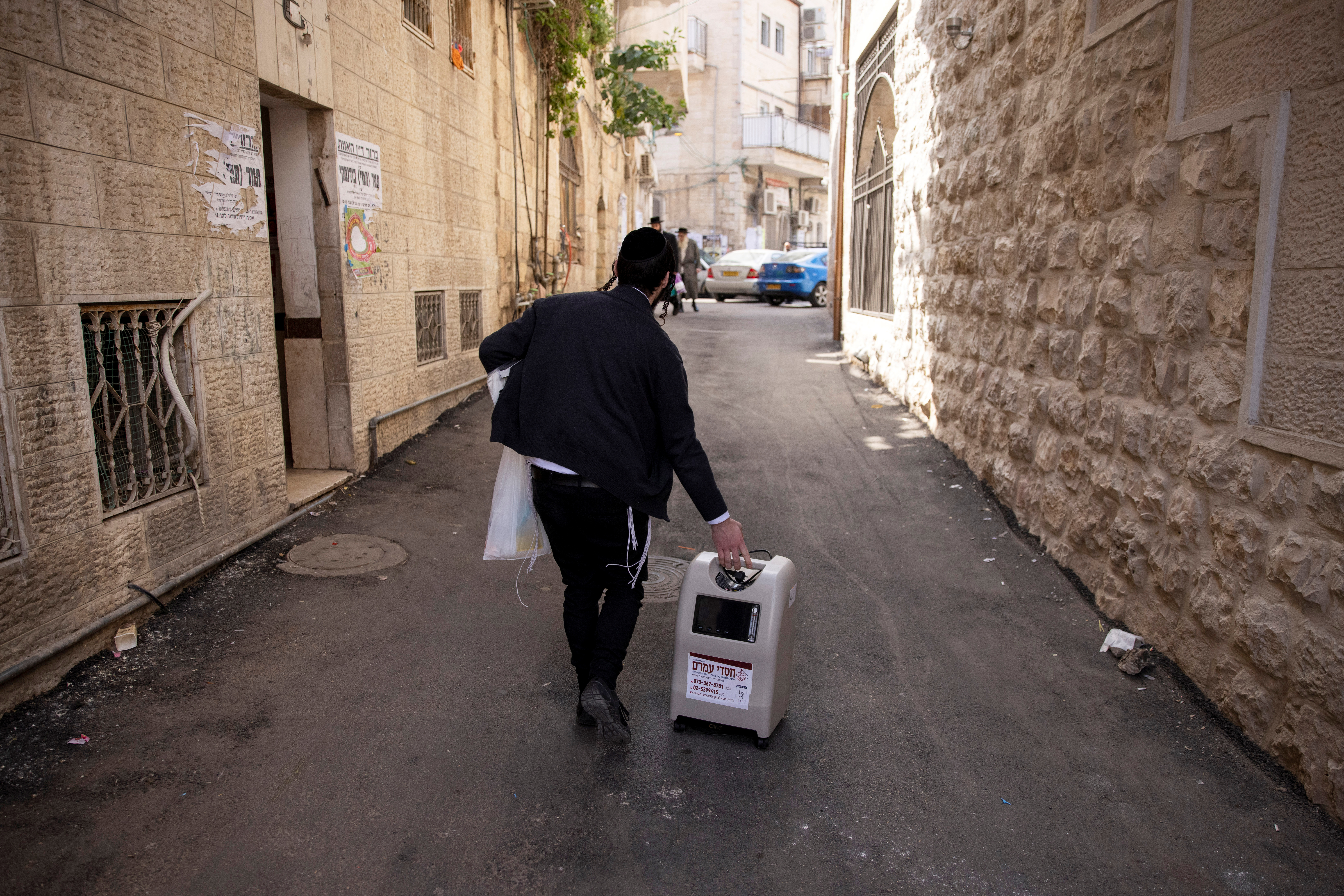 An ultra-Orthodox Jewish volunteer from Chasdei Amram, which provides home relief to people affected by the coronavirus coronavirus disease (COVID-19), carries a home oxygen concentrator as he makes his way in Jerusalem March 2, 2021. Picture taken March 2, 2021. REUTERS/Ronen Zvulun