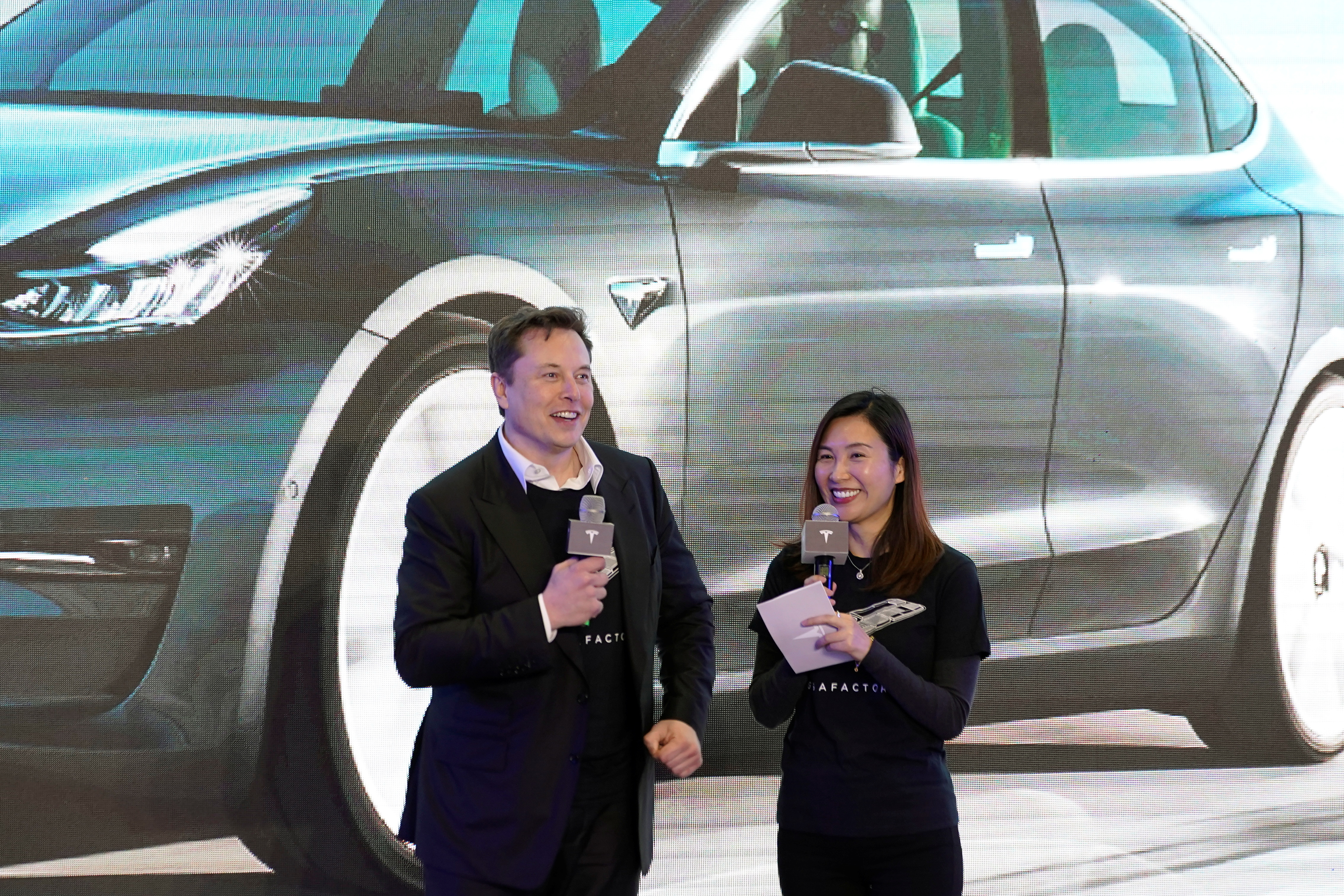 Tesla Inc CEO Elon Musk and Grace Tao, Tesla's vice president for external relations, attend a delivery ceremony for the electric vehicle (EV) maker's China-made Model 3 cars in Shanghai, China January 7, 2020. REUTERS/Aly Song