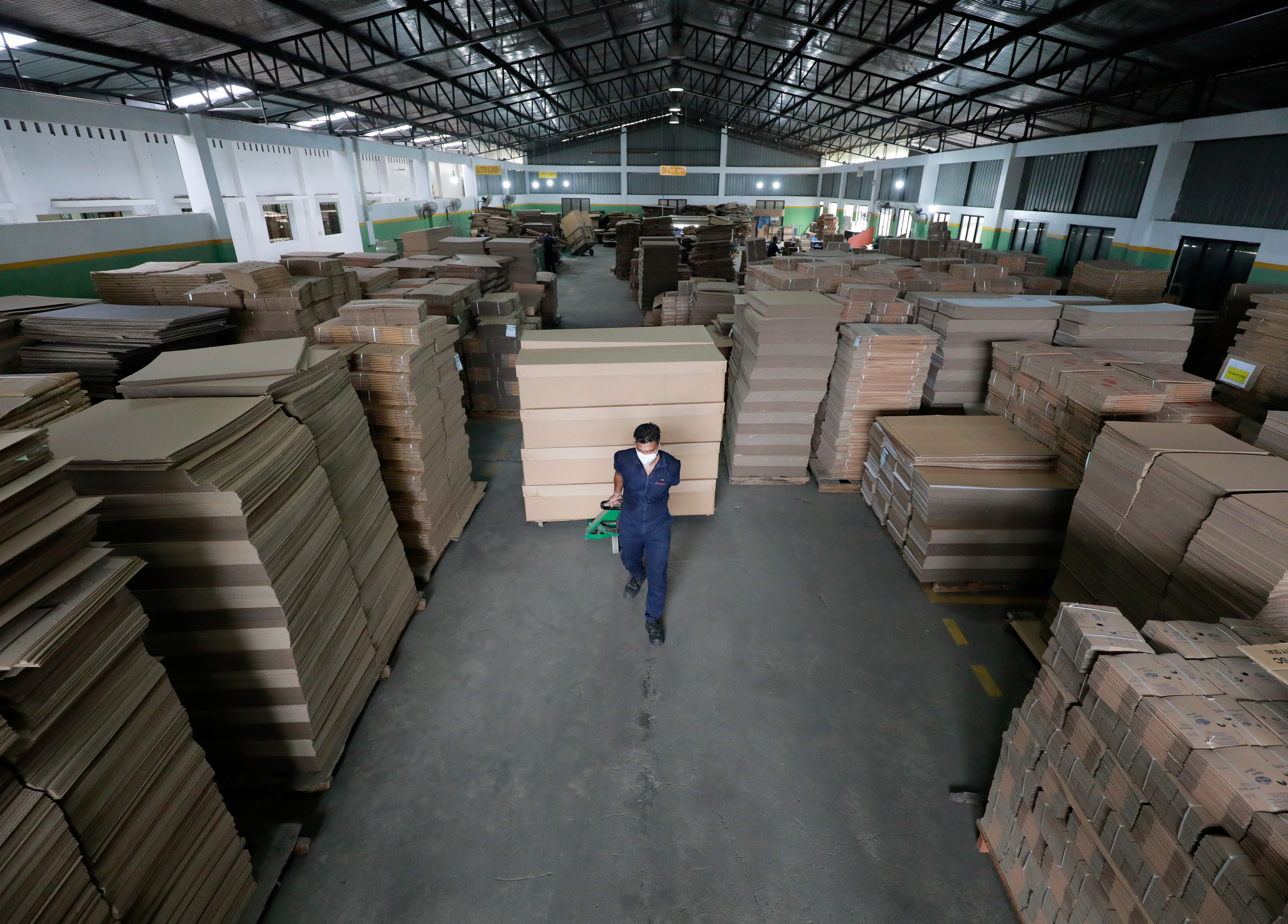 A worker carries cardboard coffins to load into a truck at a factory, amid the coronavirus disease (COVID-19) pandemic, on the outskirts of Colombo, Sri Lanka August 7, 2021. Picture taken August 7, 2021. REUTERS/Dinuka Liyanawatte