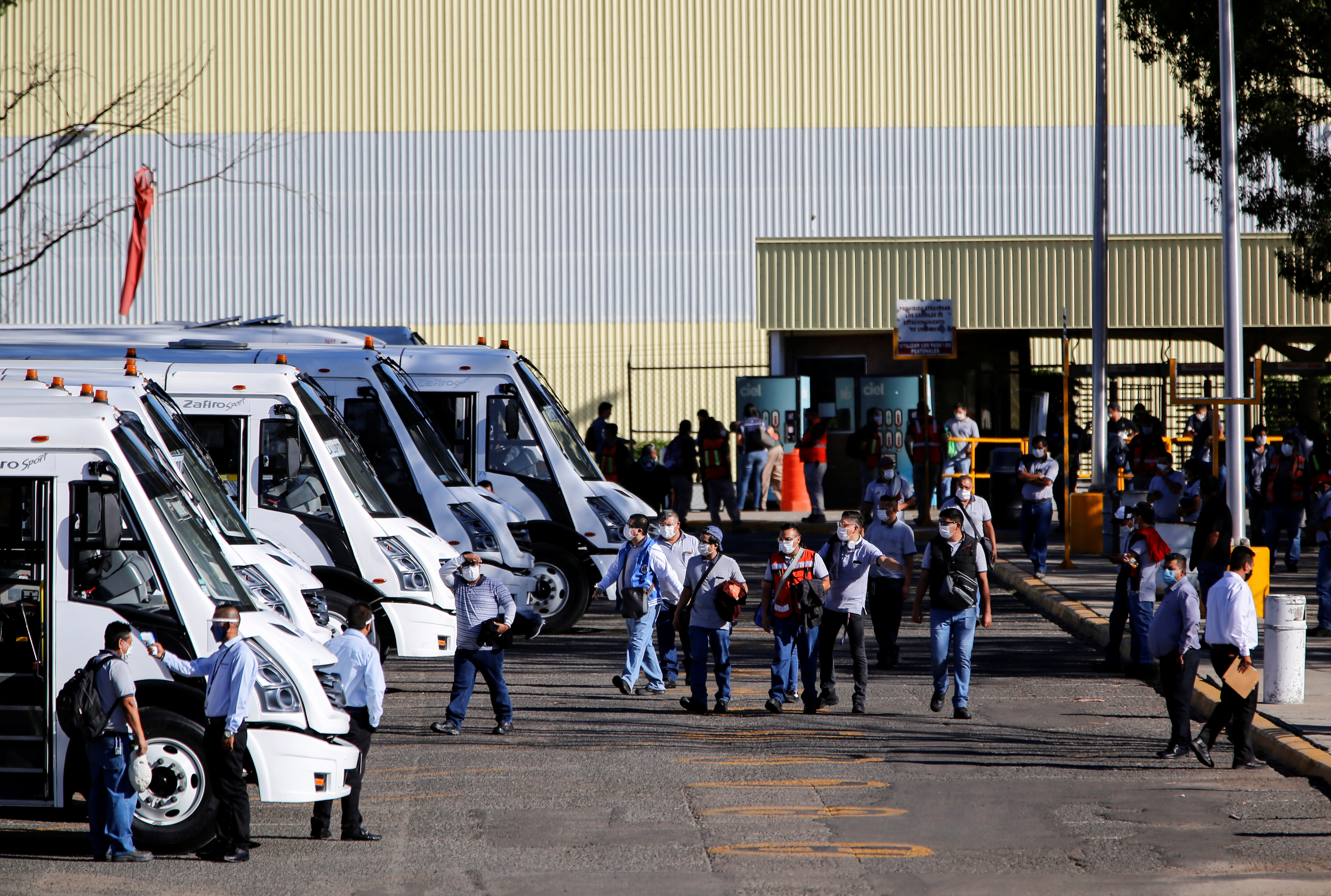 Workers leave after finishing their shift at the GM truck assembly plant as the company gradually restart operations at their Mexican facilities, amid the outbreak of the coronavirus disease (COVID-19), in Silao, Mexico May 22, 2020. REUTERS/Sergio Maldonado