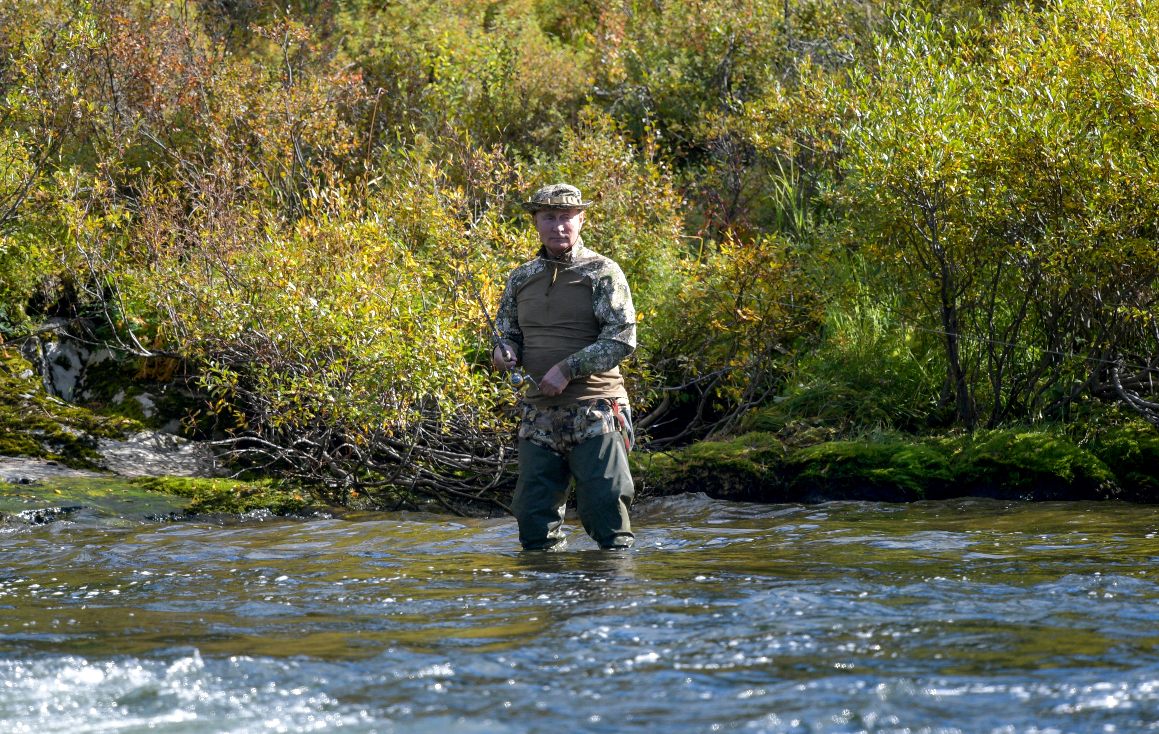 Russian President Vladimir Putin fishes during a short vacation at an unknown location in Siberia, Russia, in this undated photo taken in September 2021 and released September 26, 2021. Sputnik/Alexei Druzhinin/Kremlin via REUTERS
