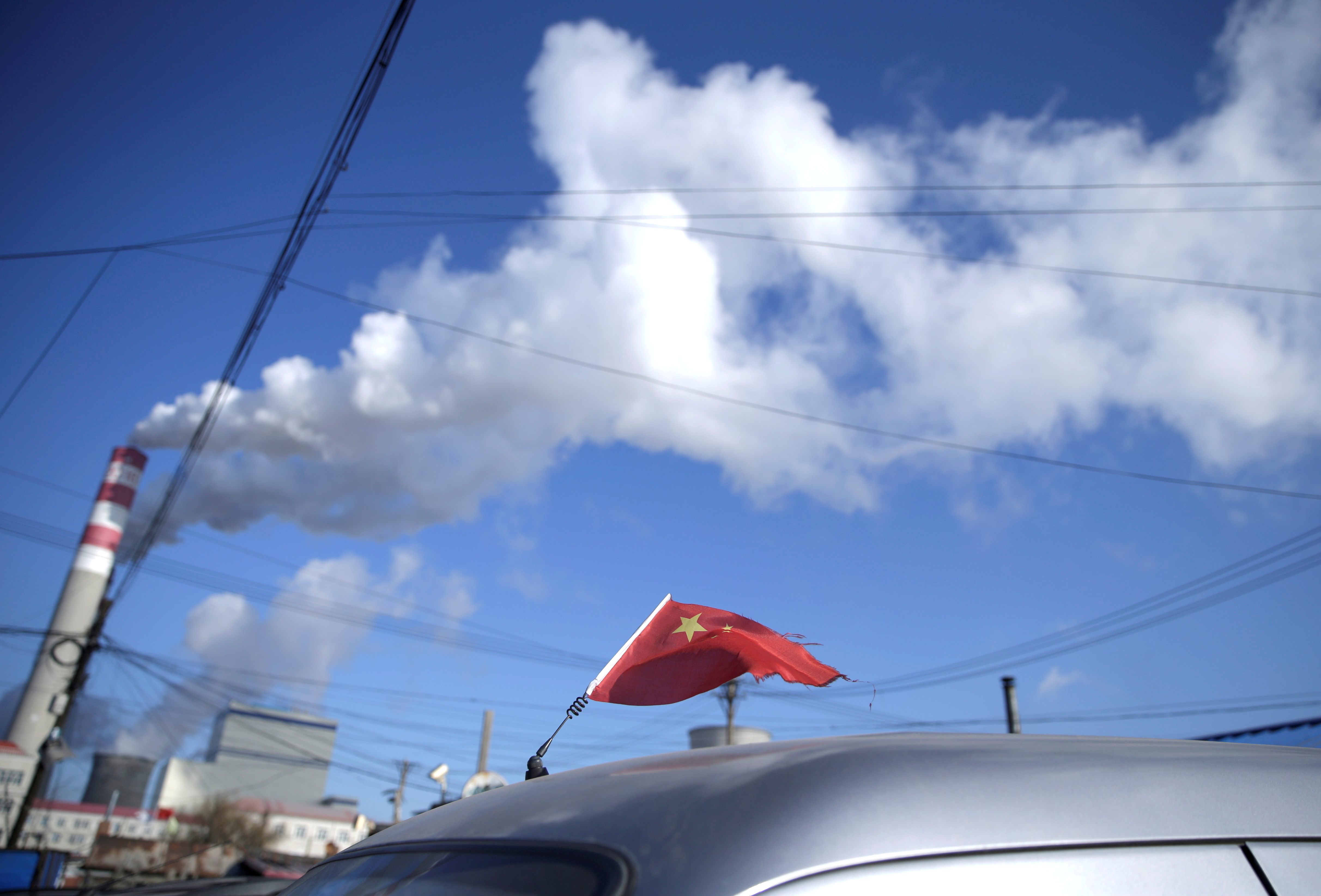 A Chinese flag is seen on the top of a car near a coal-fired power plant in Harbin, Heilongjiang province, China November 27, 2019. REUTERS/Jason Lee/File Photo