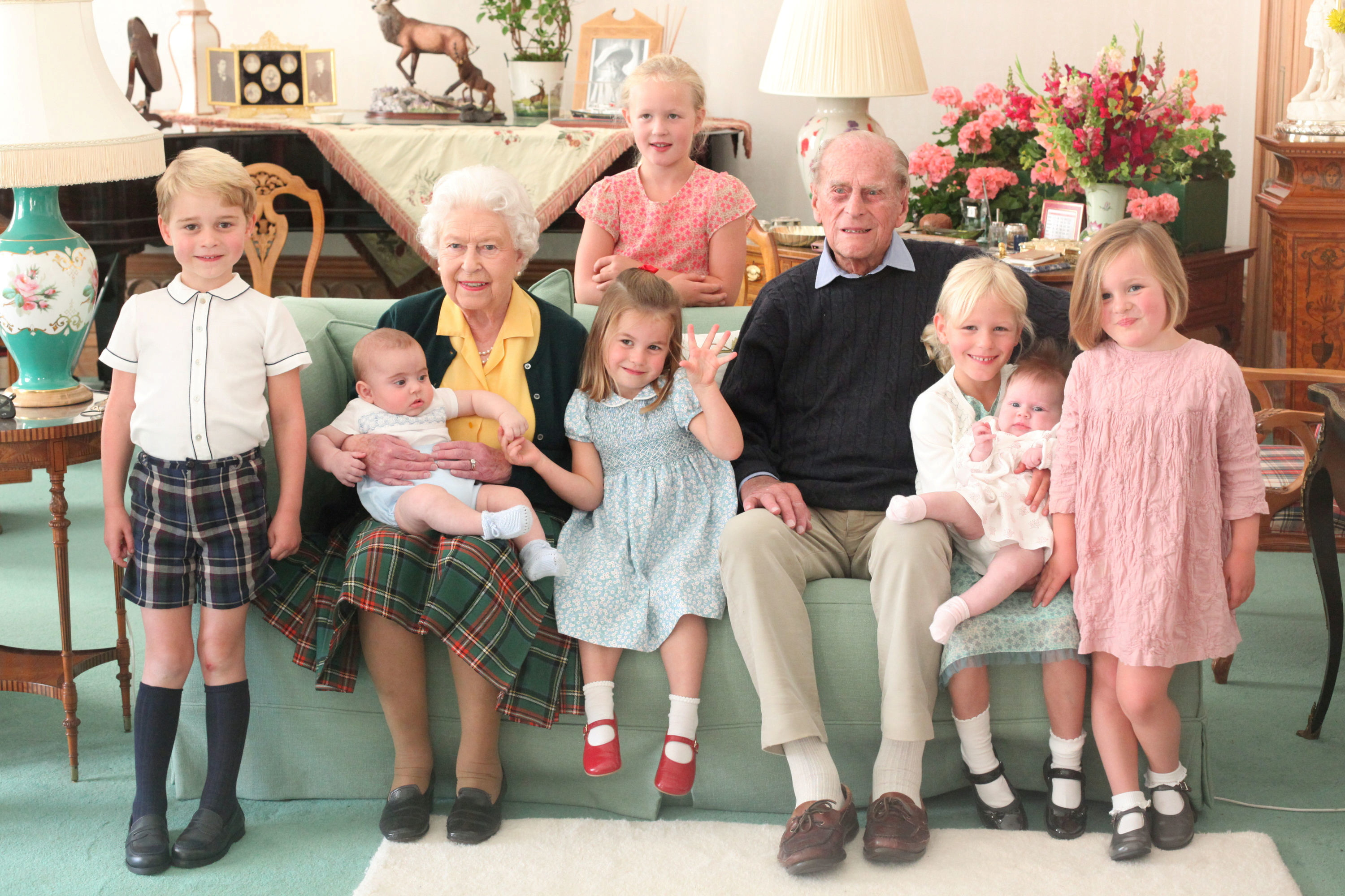 Britain's Queen Elizabeth and Prince Philip sit with Prince George, Prince Louis, Savannah Phillips, Princess Charlotte, Isla Phillips, Lena Tindall, and Mia Tindall in this undated picture released on April 14, 2021. The Duchess of Cambridge/Handout via REUTERS