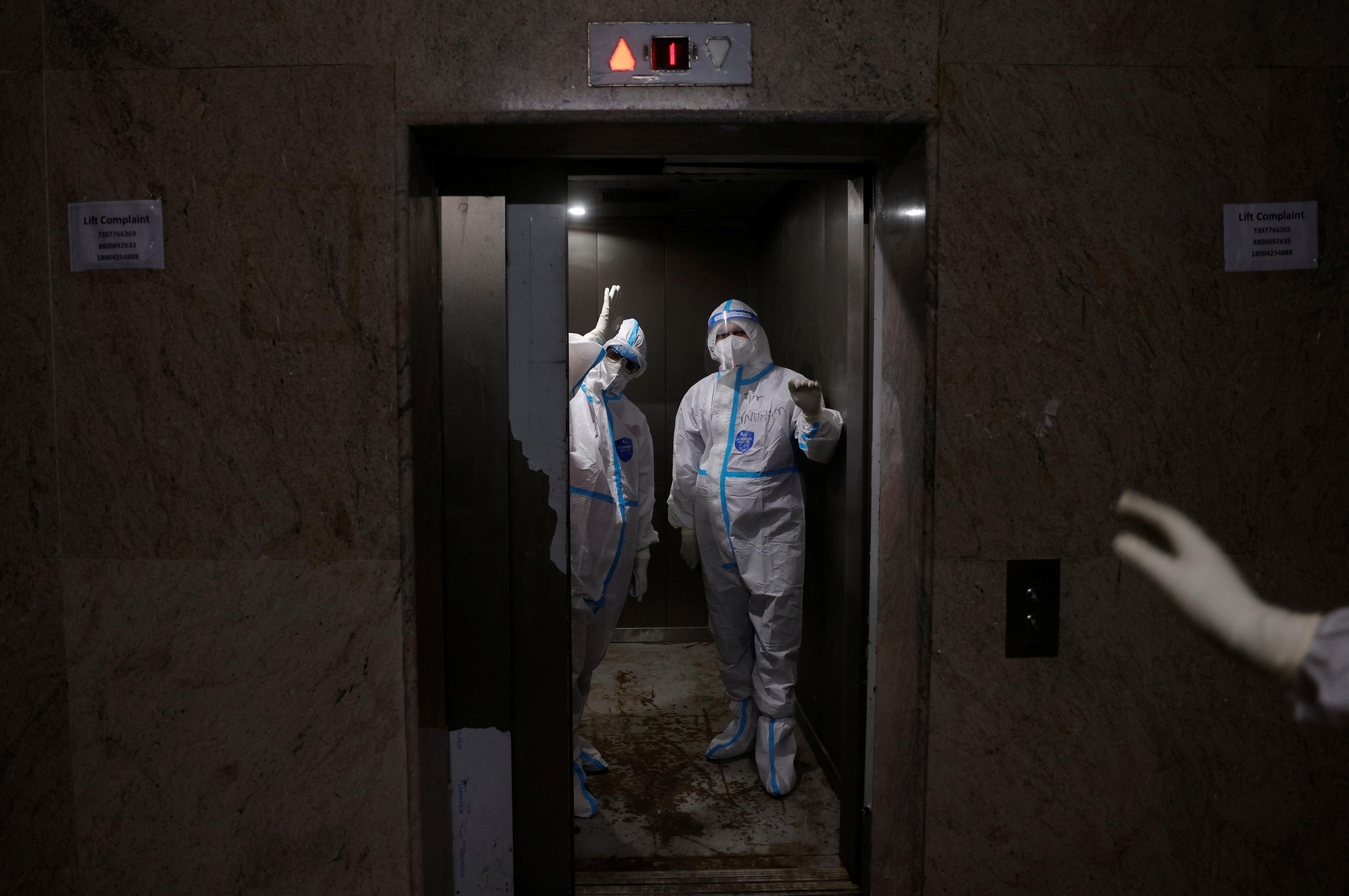 เจ้าหน้าที่ทางการแพทย์โบกมือให้เพื่อนร่วมงานขณะขึ้นลิฟต์ไปยังหอผู้ป่วยหนัก (ICU) สำหรับผู้ป่วยโรคโคโรนาไวรัส (COVID-19) ที่โรงพยาบาลสถาบันวิทยาศาสตร์การแพทย์ของรัฐบาล (GIMS) ในเกรทเตอร์นอยดาในเขตชานเมือง แห่งนิวเดลีอินเดีย 21 พฤษภาคม 2021 REUTERS / Adnan Abidi
