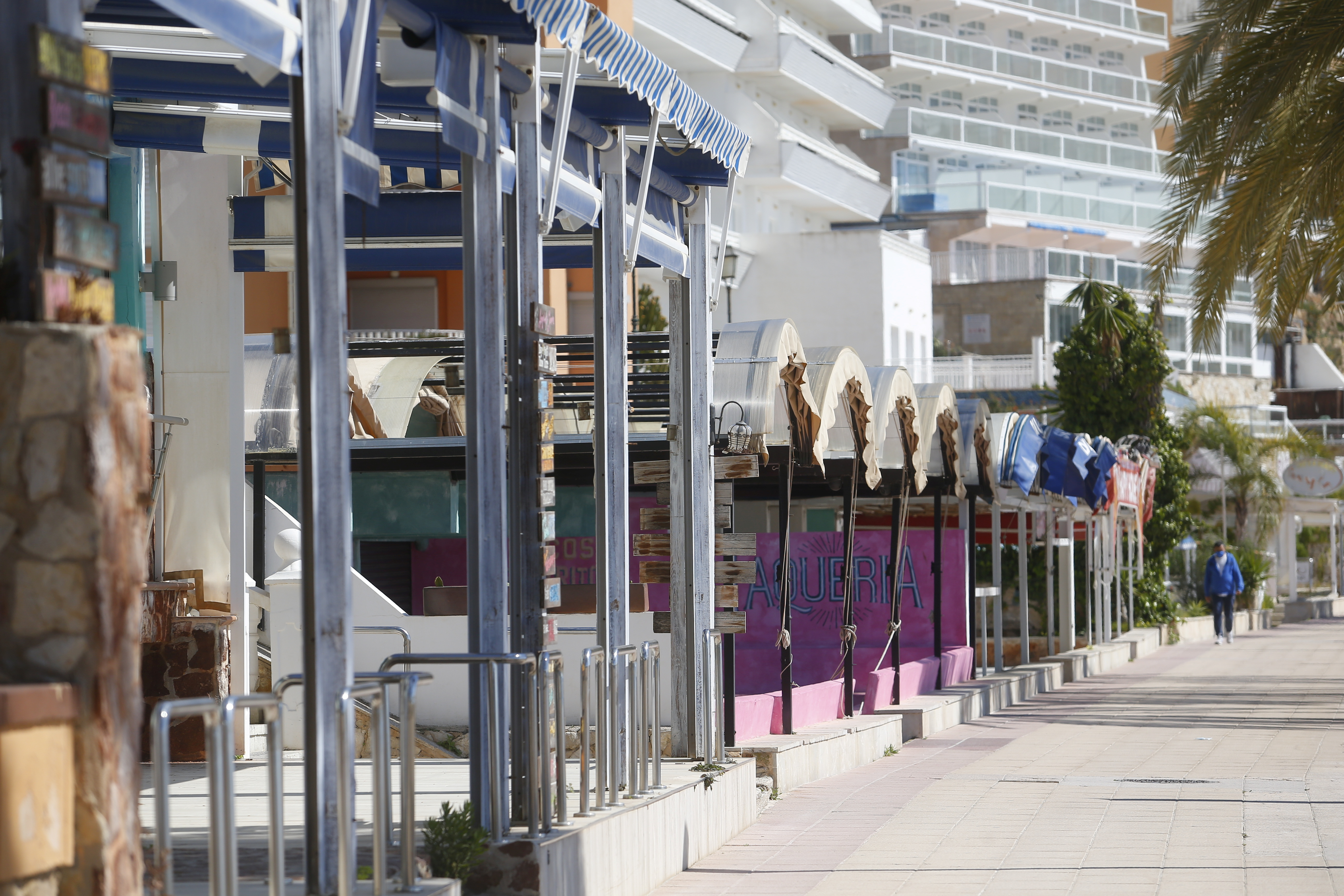 A man walks next to closed terrace bars in Magaluf beach sea promenade in the Spanish island of Mallorca, as many commerces remain closed in the Balearic Islands, amid the coronavirus disease (COVID-19) pandemic, Spain March 24, 2021. REUTERS/Enrique Calvo?