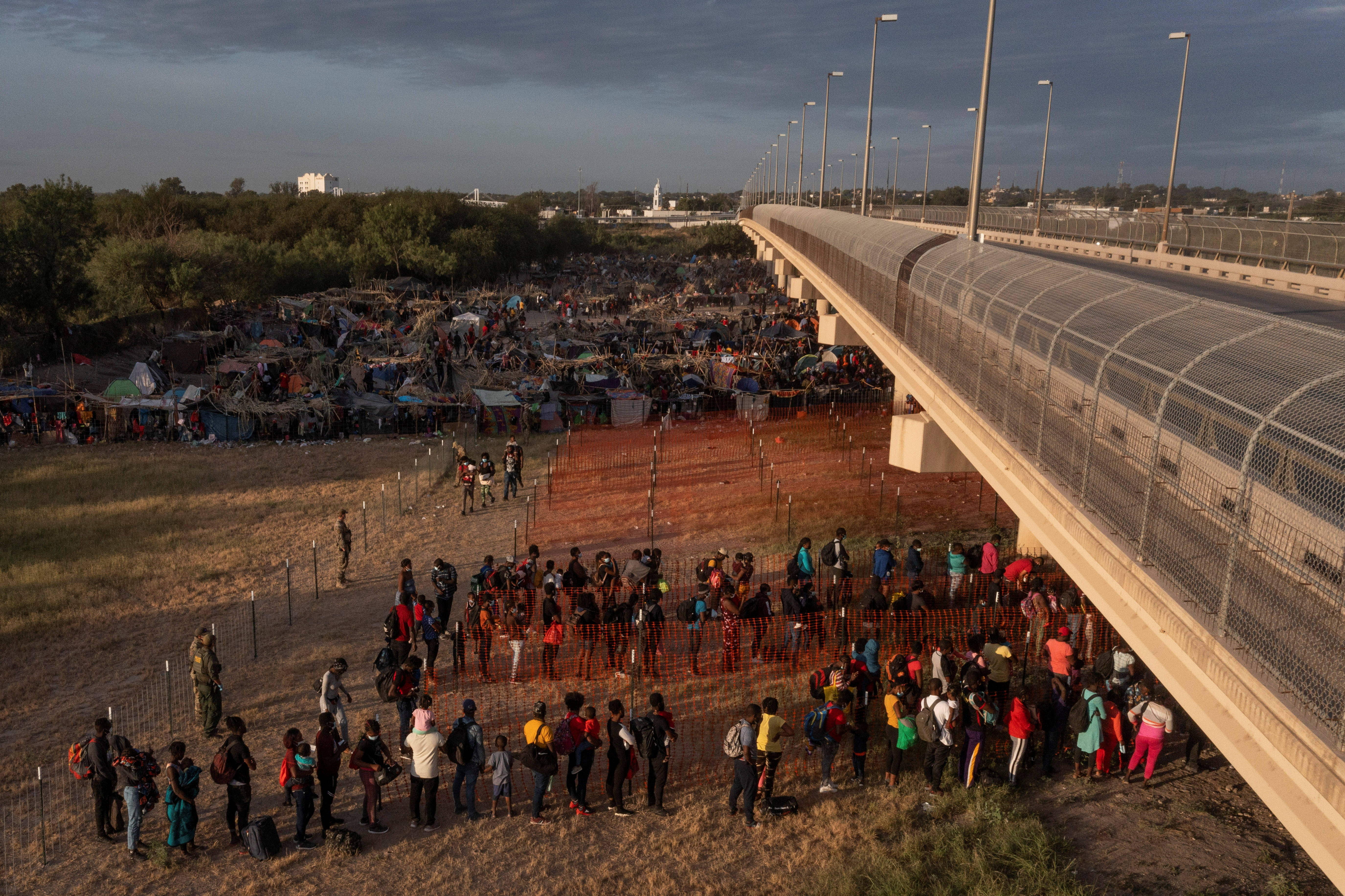 Migrants stand in line while awaiting transport out of a border makeshift camp along the International Bridge in Del Rio, Texas, U.S., September 22, 2021. Picture taken with a drone. REUTERS/Adrees Latif