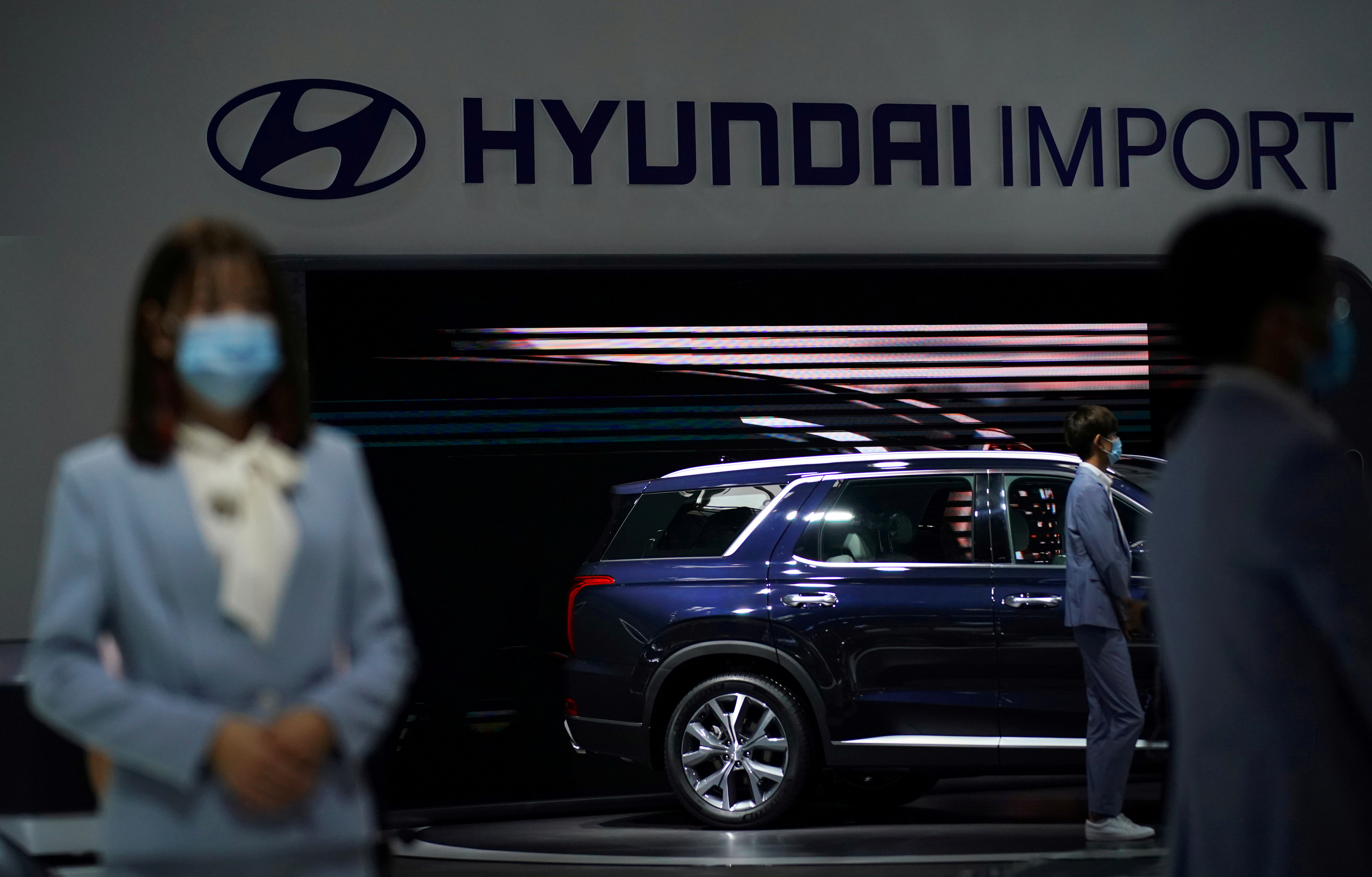 Staff members wearing face masks are seen at a Hyundai booth at the Beijing International Automotive Exhibition, or Auto China show, in Beijing, China September 27, 2020. REUTERS/Tingshu Wang/File Photo