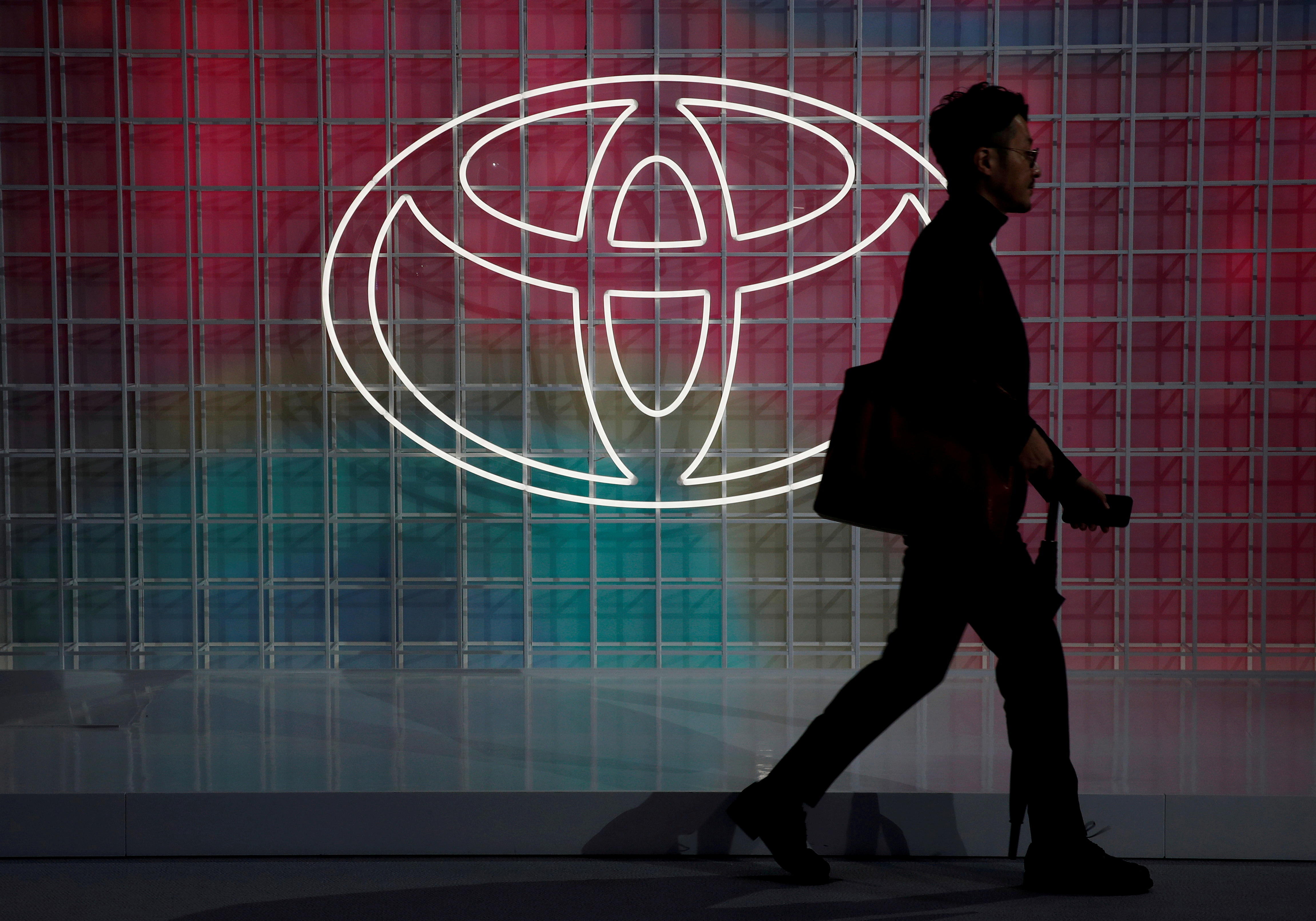 A man walks past a Toyota logo at the Tokyo Motor Show, in Tokyo, Japan October 24, 2019. REUTERS/Edgar Su/File Photo