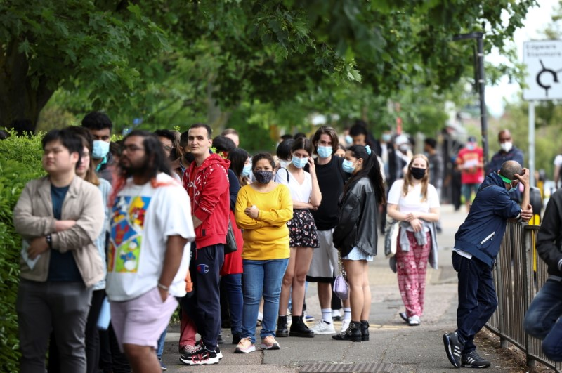 People queue outside a vaccination centre for those aged over 18 years old at the Belmont Health Centre in Harrow,  in London, Britain, June 6, 2021. REUTERS/Henry Nicholls