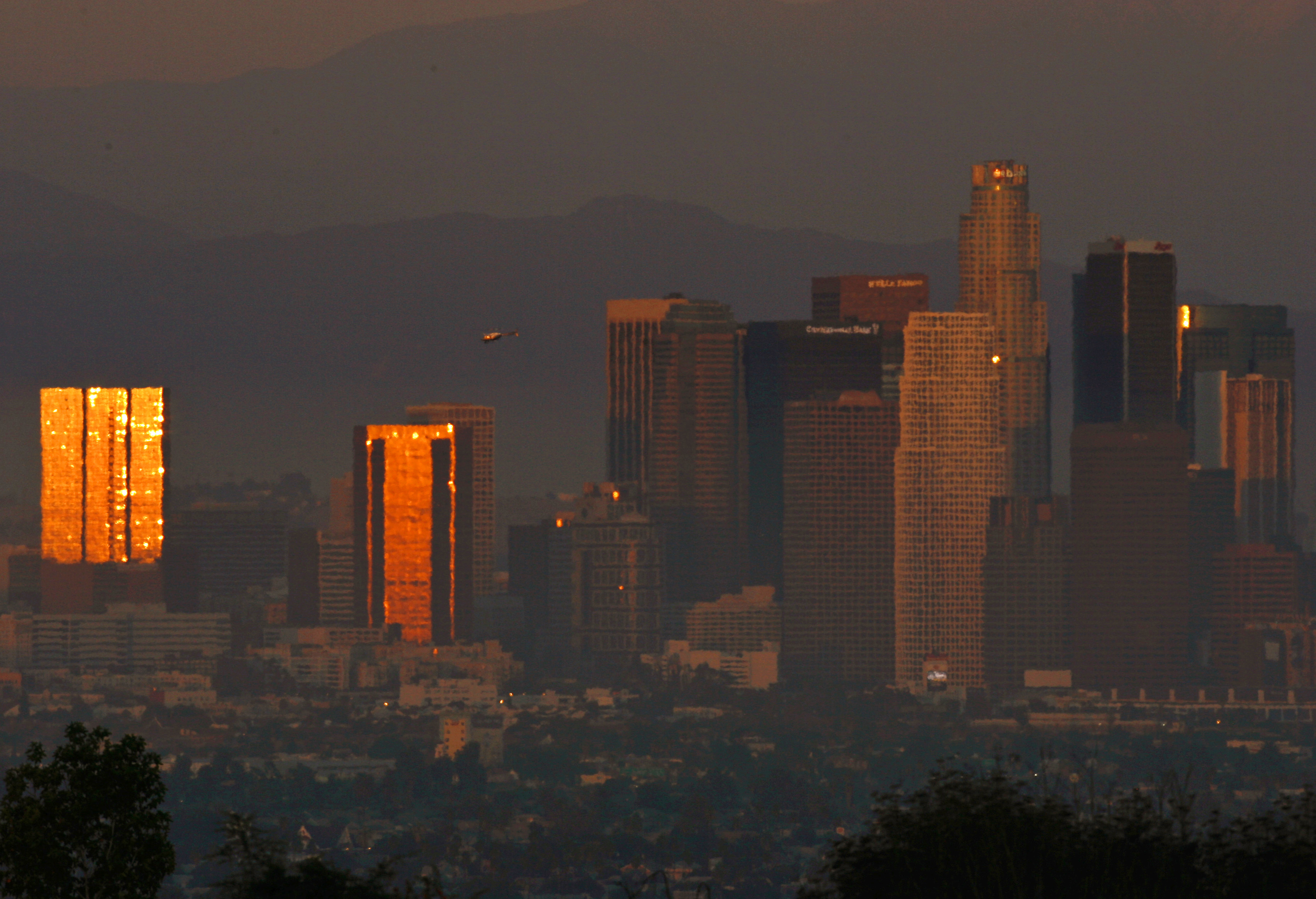 The sun reflects on downtown skyscrapers as it sets through the Los Angeles smog and haze, October 22, 2006.  REUTERS/Lucy Nicholson (UNITED STATES)