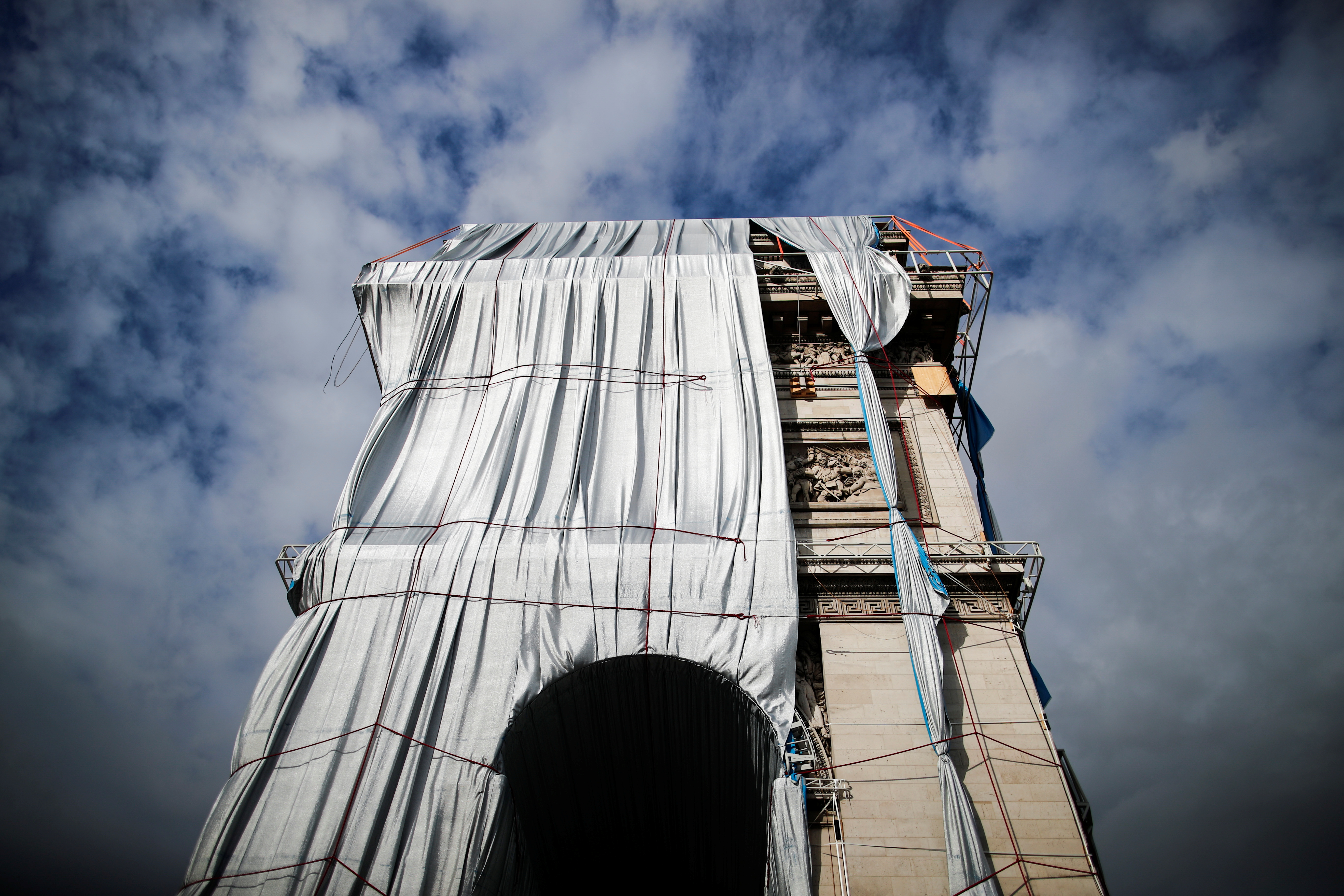 Rope access technicians work on the removal of the fully wrapped Arc de Triomphe monument, after it was wrapped for an art installation entitled 'L'Arc de Triomphe, Wrapped' conceived by the late artists Christo and Jeanne-Claude, on the Champs-Elysees avenue in Paris, France, October 4, 2021. REUTERS/Benoit Tessier