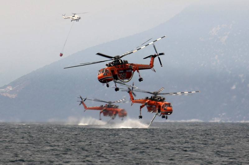 Firefightering helicopters are filled with water off the beach of the village of Pefki, on the island of Evia, Greece, August 10, 2021. REUTERS/Nicolas Economou
