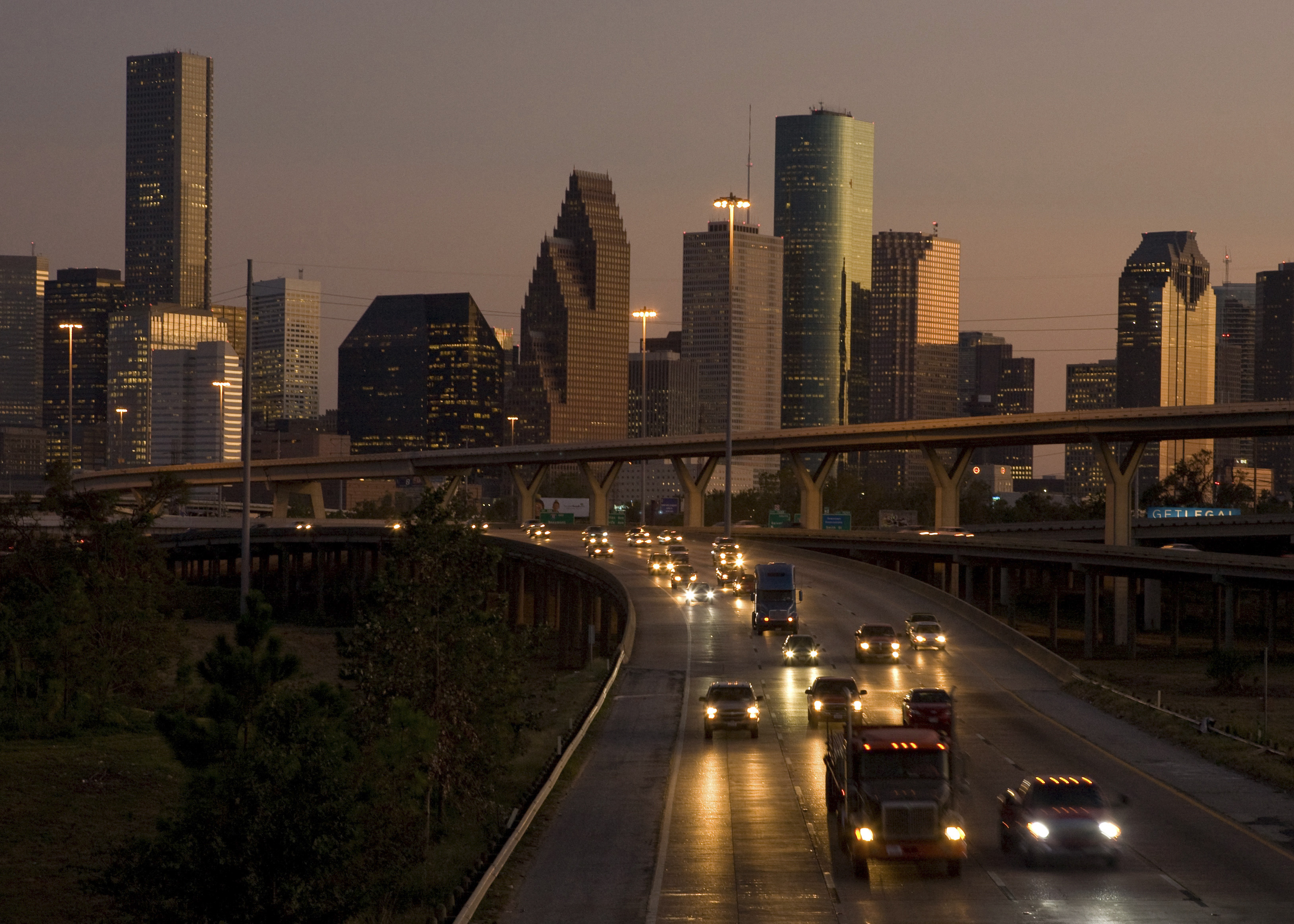 Traffic flows at dusk with the downtown Houston skyline in the background as night falls.   REUTERS/Richard Carson